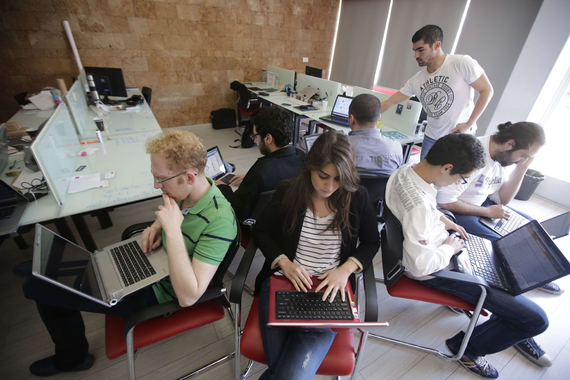 Genuine concerns. Lebanese entrepreneurs from different internet startup companies work in the offices of a startup accelerator in Beirut's Hamra district.     (AFP)