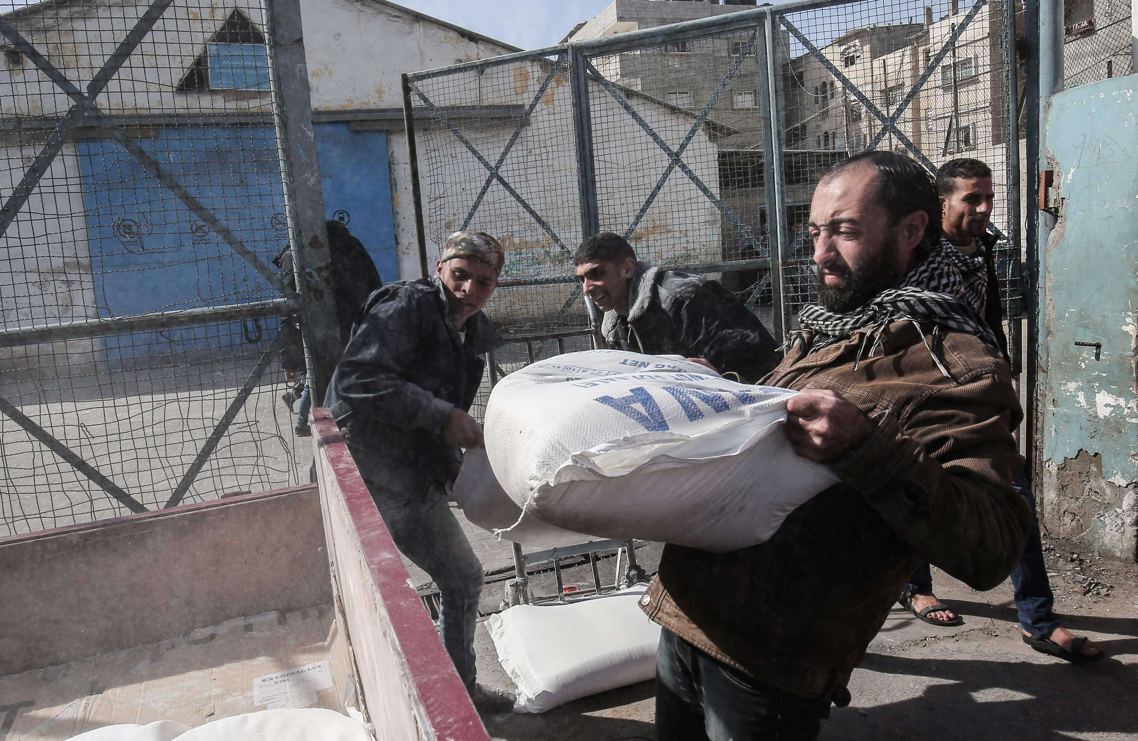 Heavy blow. Palestinian refugees collect aid parcels at a UN food distribution centre in Rafah, on January 21.(AFP)