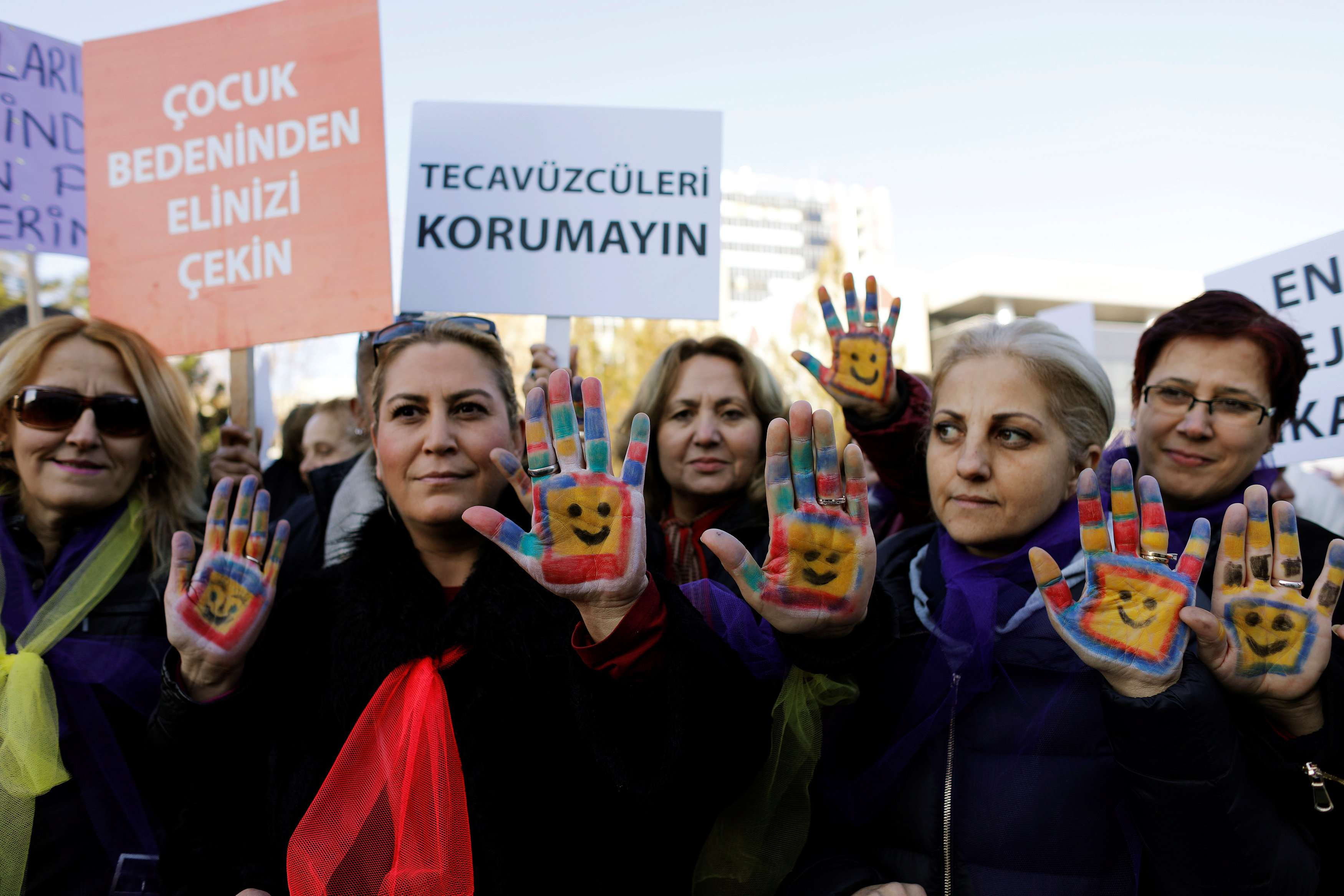 "Public outcry. Protesters show their painted hands and raise banners that read ""Keep your hands off from a child's body"" (L) and ""Don't protect the rapists"" (R) during a protest in front of the Turkish Parliament in Ankara. (Reuters)"