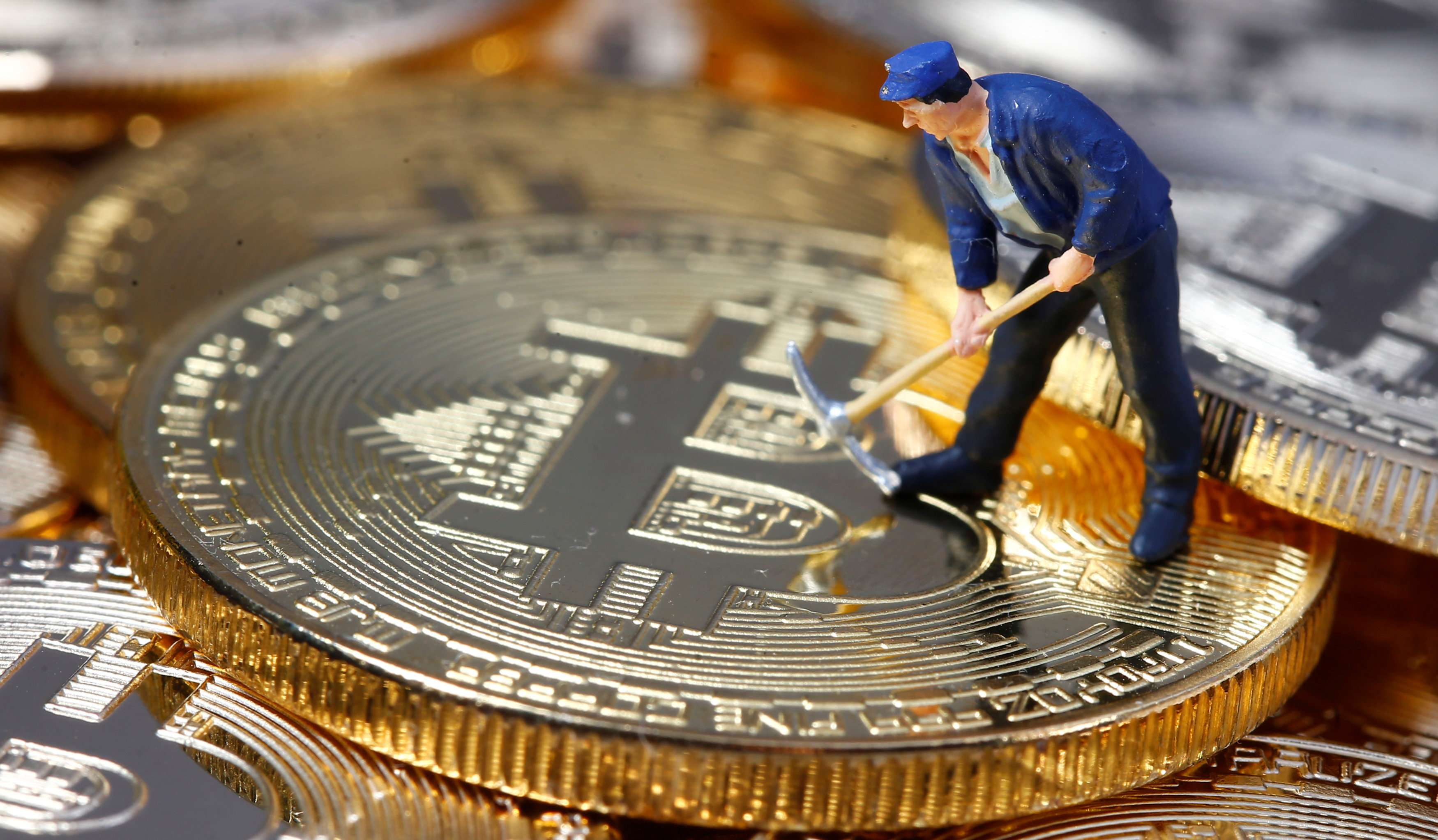 A small toy figure is seen on representations of the Bitcoin virtual currency in this illustration picture. (Reuters)