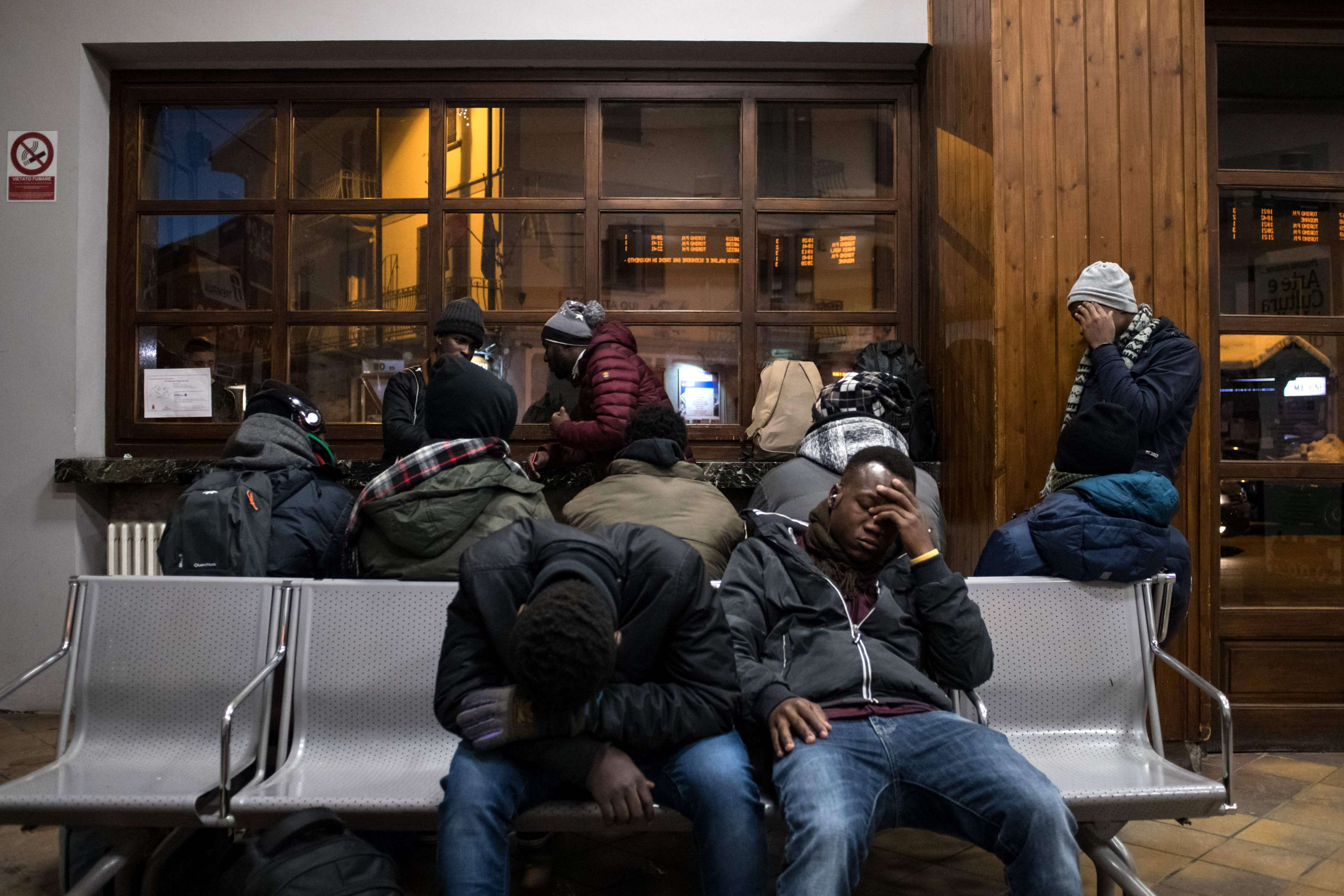 Migrants rest in the waiting hall of the train station in Italy's Bardonecchia, on January 13.   (AFP)
