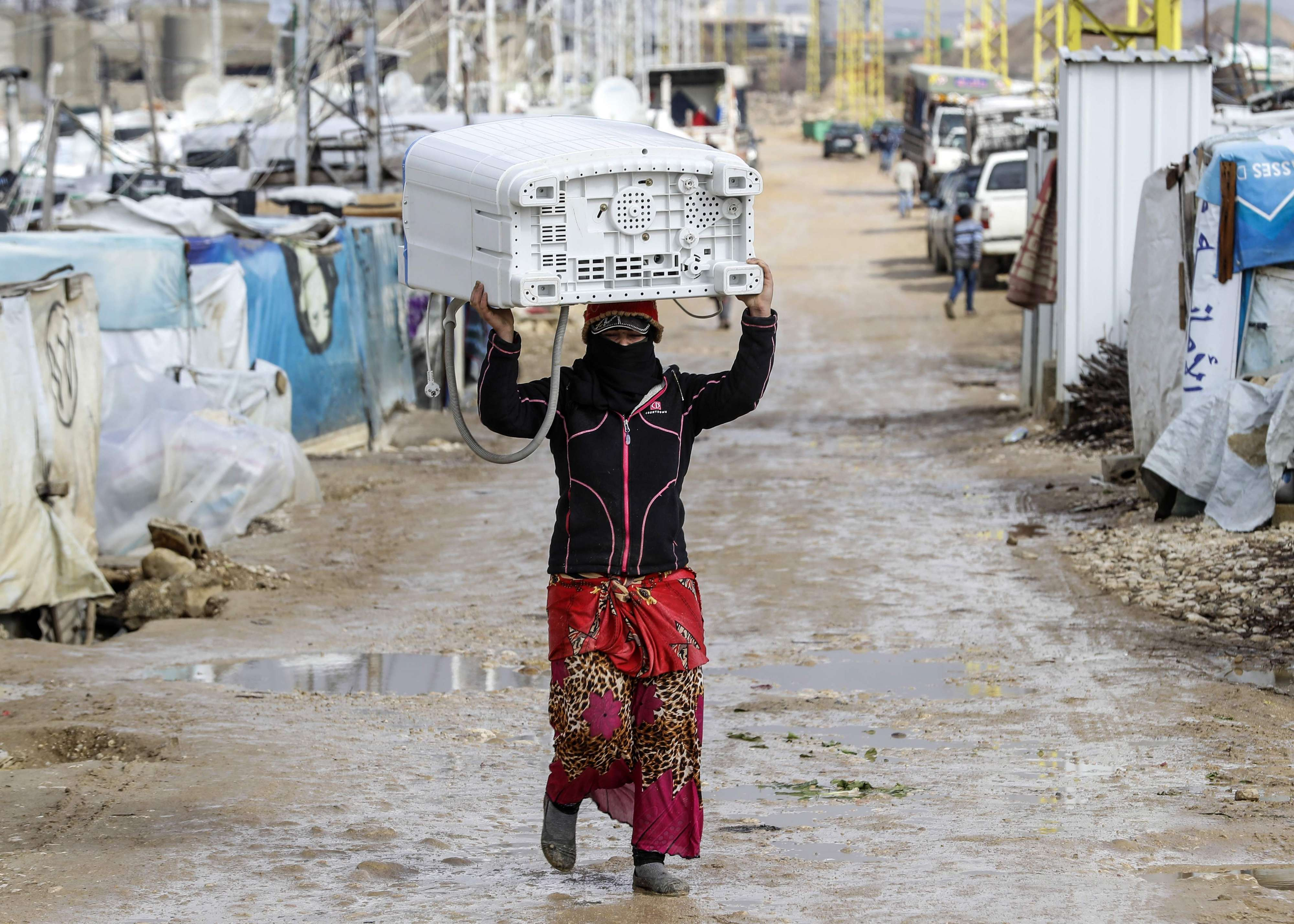 A Syrian woman carries a washing machine above her head as she walks down through the tents and shelters at a refugee camp on the outskirts of the town of Zahle in Lebanon's Bekaa Valley, on January 26. (AFP)