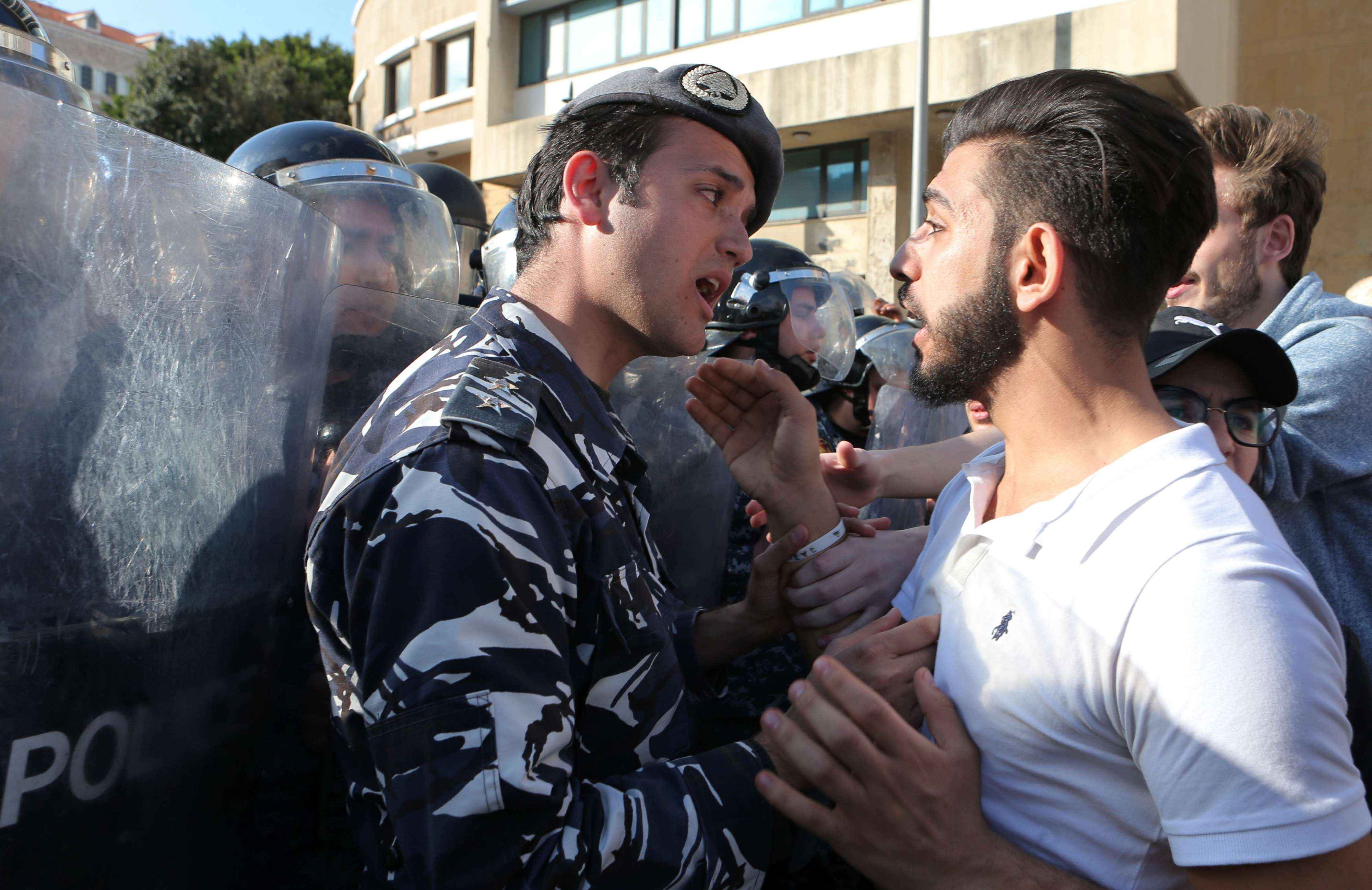 A Lebanese anti-government protester scuffles with a riot policeman during a protest in Beirut, last March. (AFP)