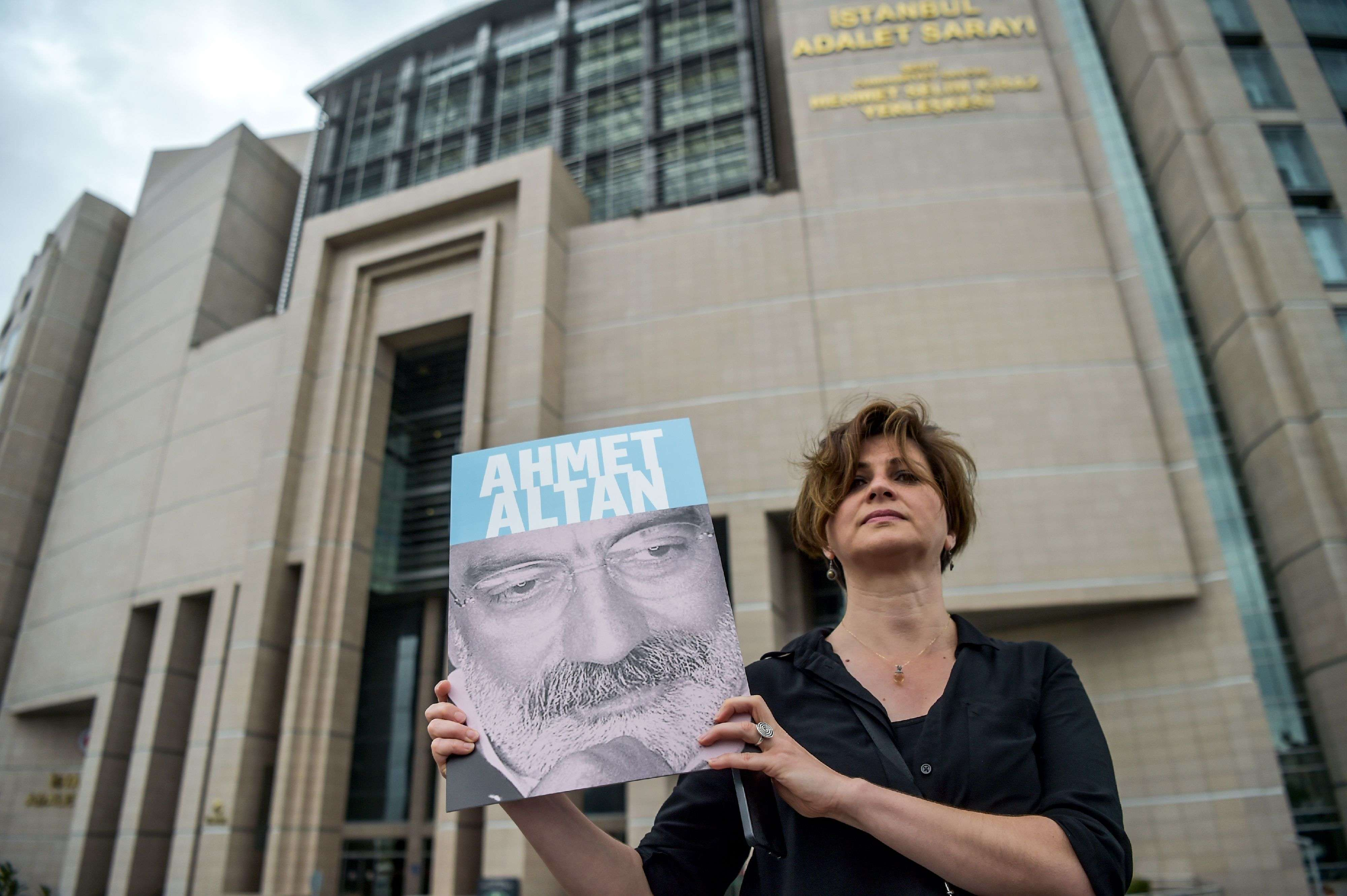 A journalist poses with a portrait of Turkish journalist Ahmet Altan in front of a courthouse in Istanbul.  (AFP)