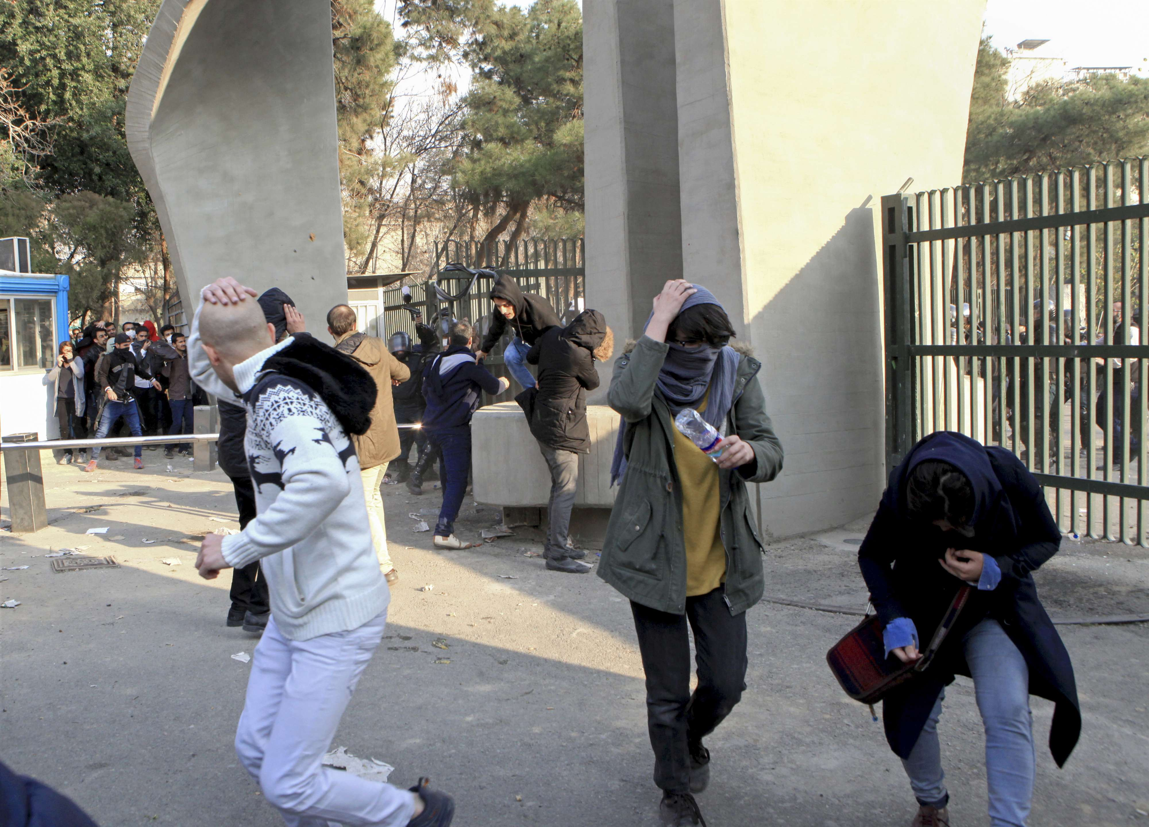 University students run away from stones thrown by police during an anti-government protest inside Tehran University, last December.  (AP)