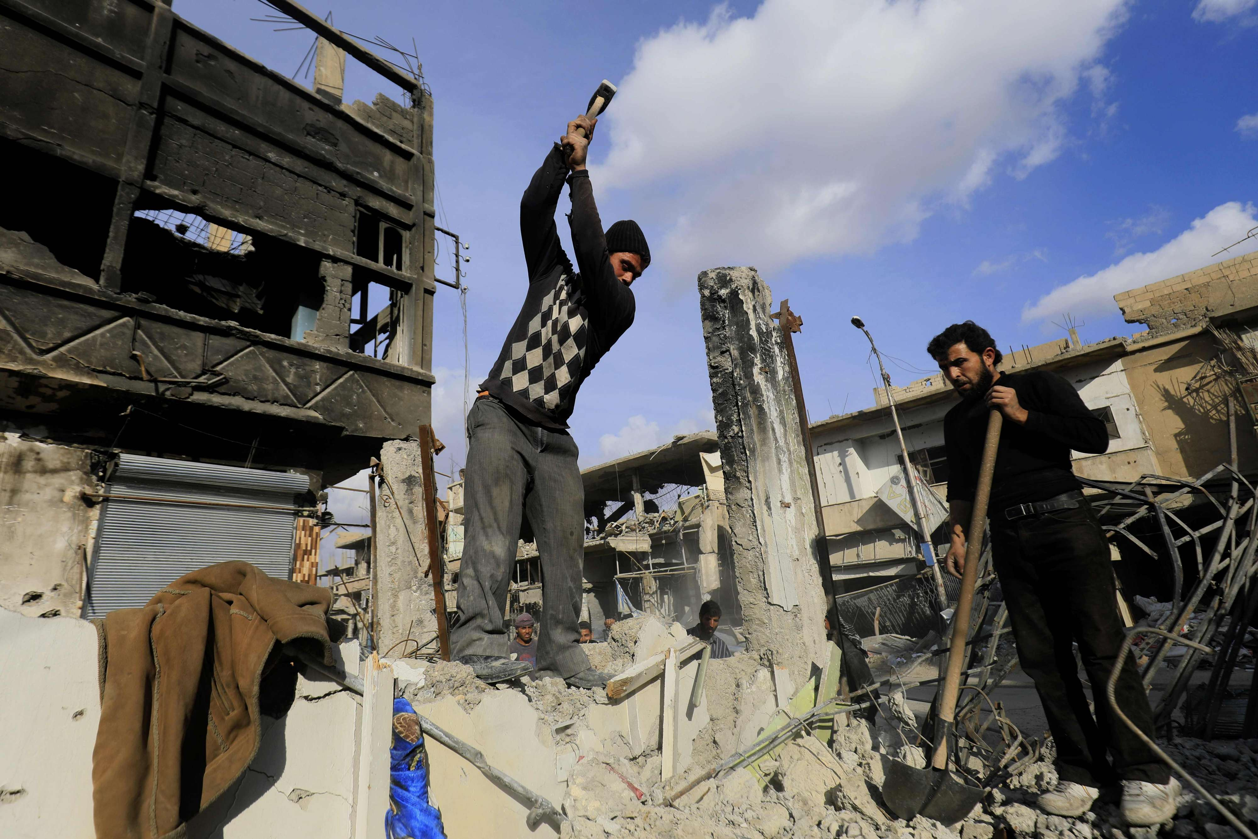 Syrian men work on reconstructing a damaged building in the northern Syrian city of Raqqa, on January 16. (AFP)