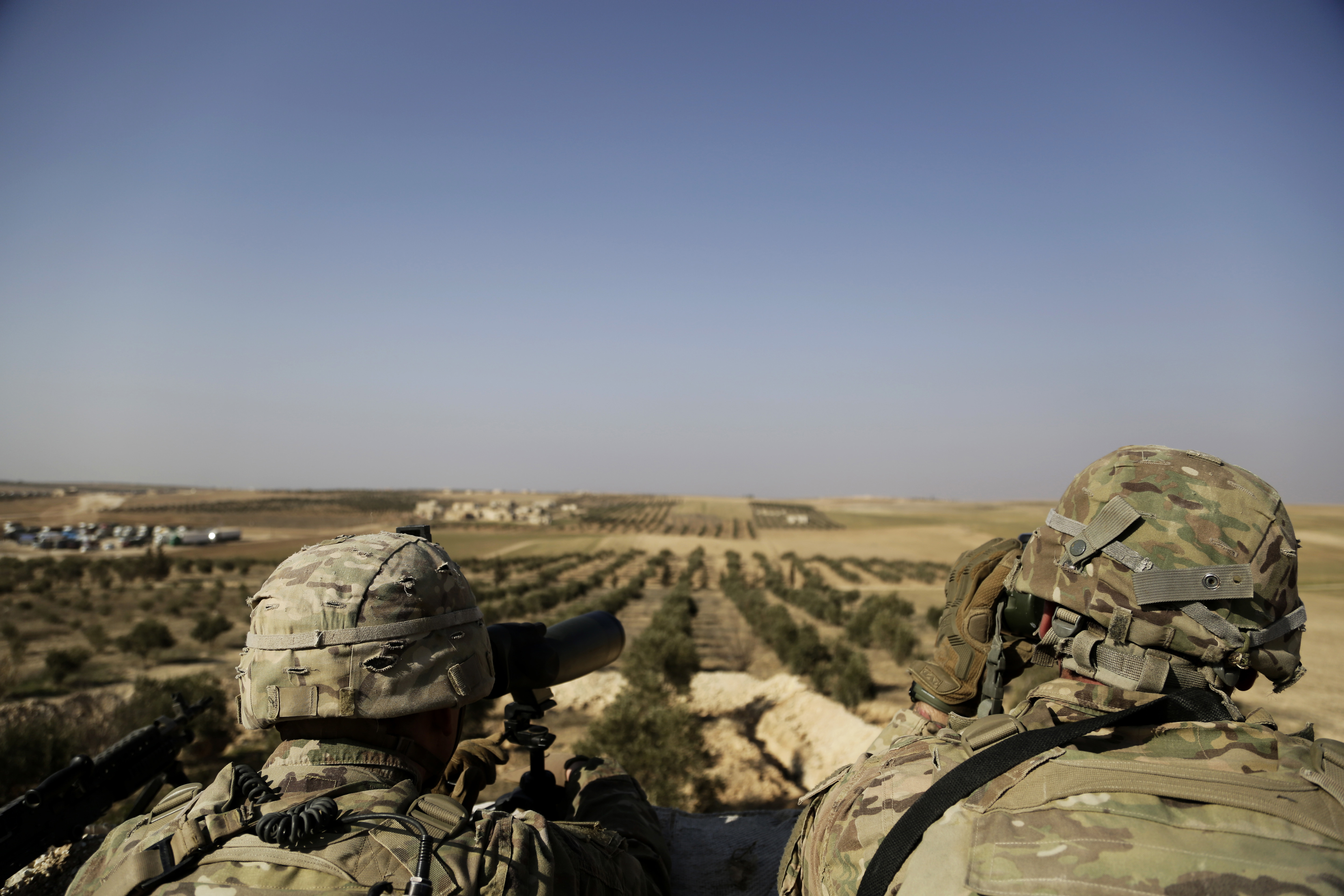 American troops look out toward the border with Turkey from a small outpost near the town of Manbij, northern Syria, Wednesday, Feb. 7, 2018. (AP Photo)