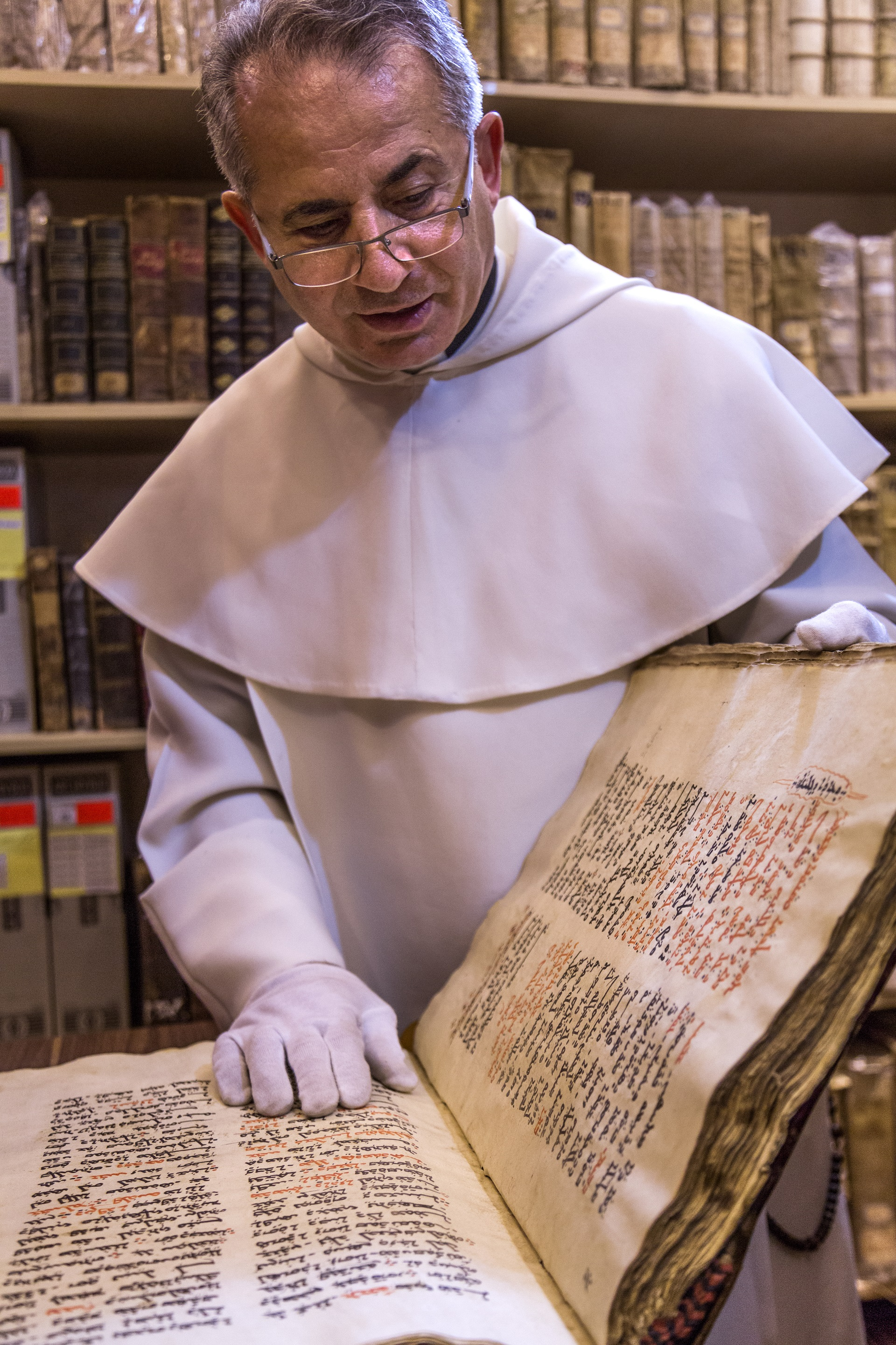 Iraqi Dominican monk, Father Najeeb  Michaeel, looks at an ancient manuscript. (Richard Wilding)