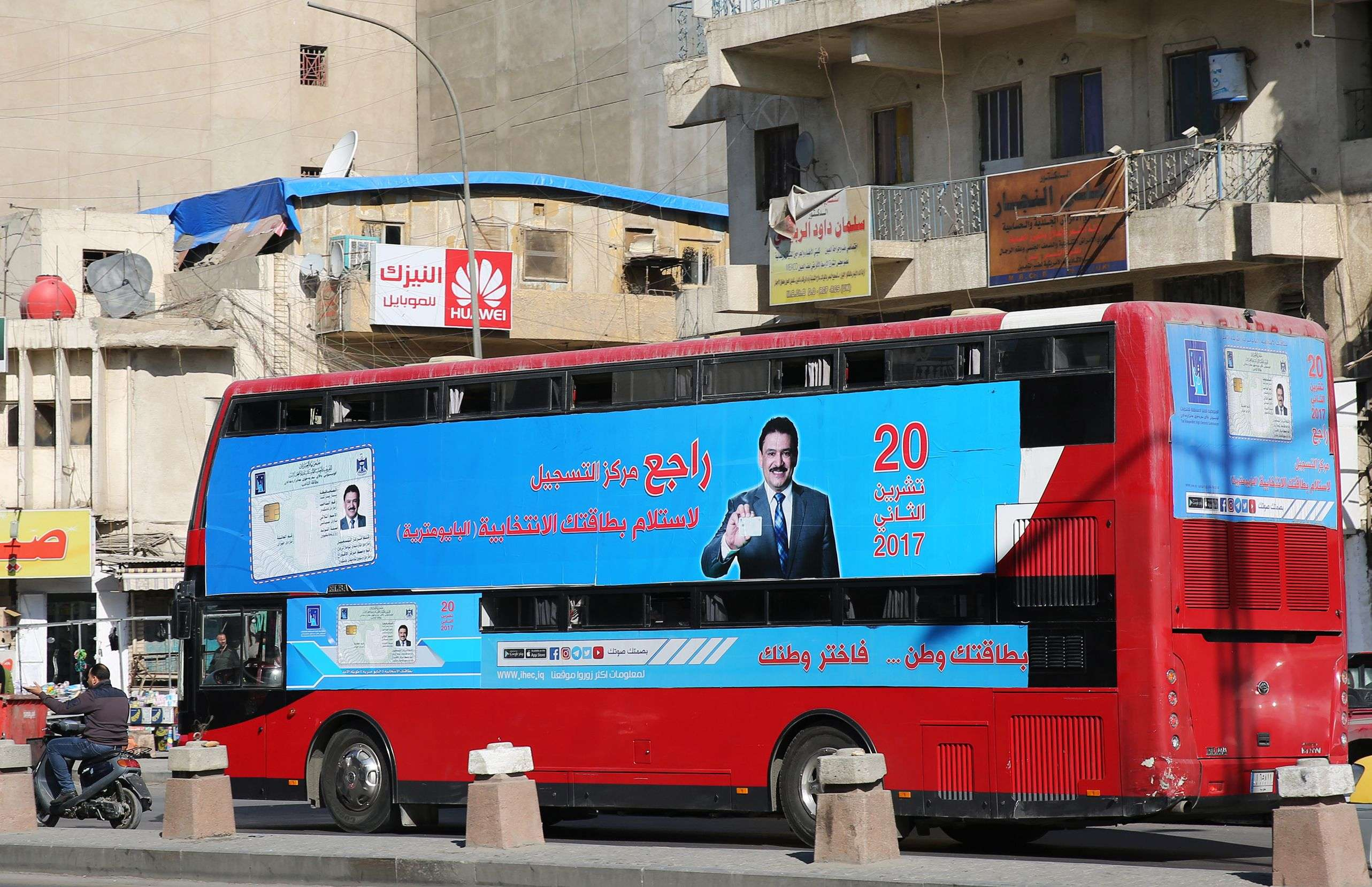 A bus displays a poster advising people to check about their voting information ahead of Iraq's parliamentary elections Baghdad. (AFP)