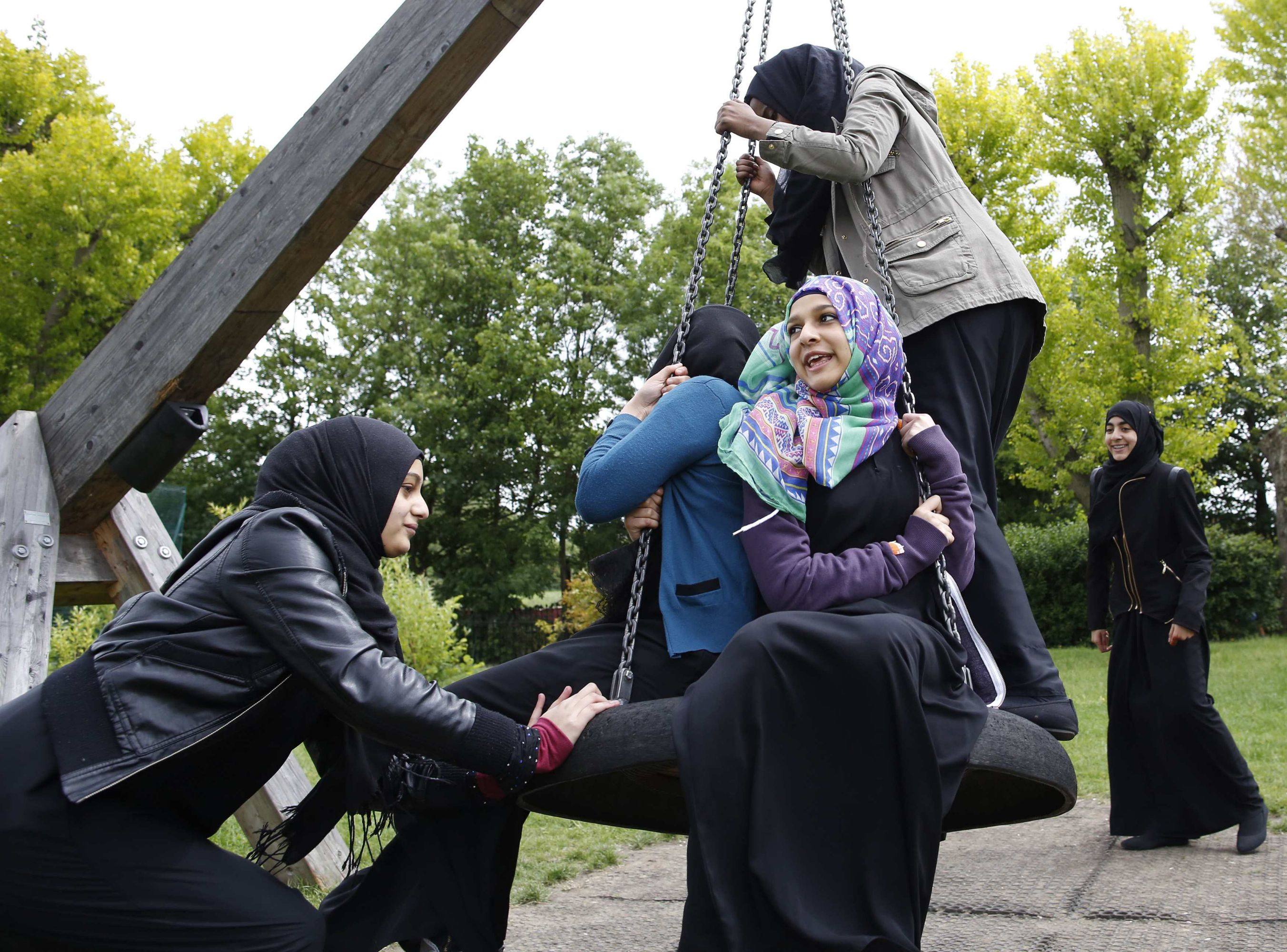 A Muslim girl pushes her friend on a swing after finishing a GCSE exam near their school in Hackney in east London. (Reuters)