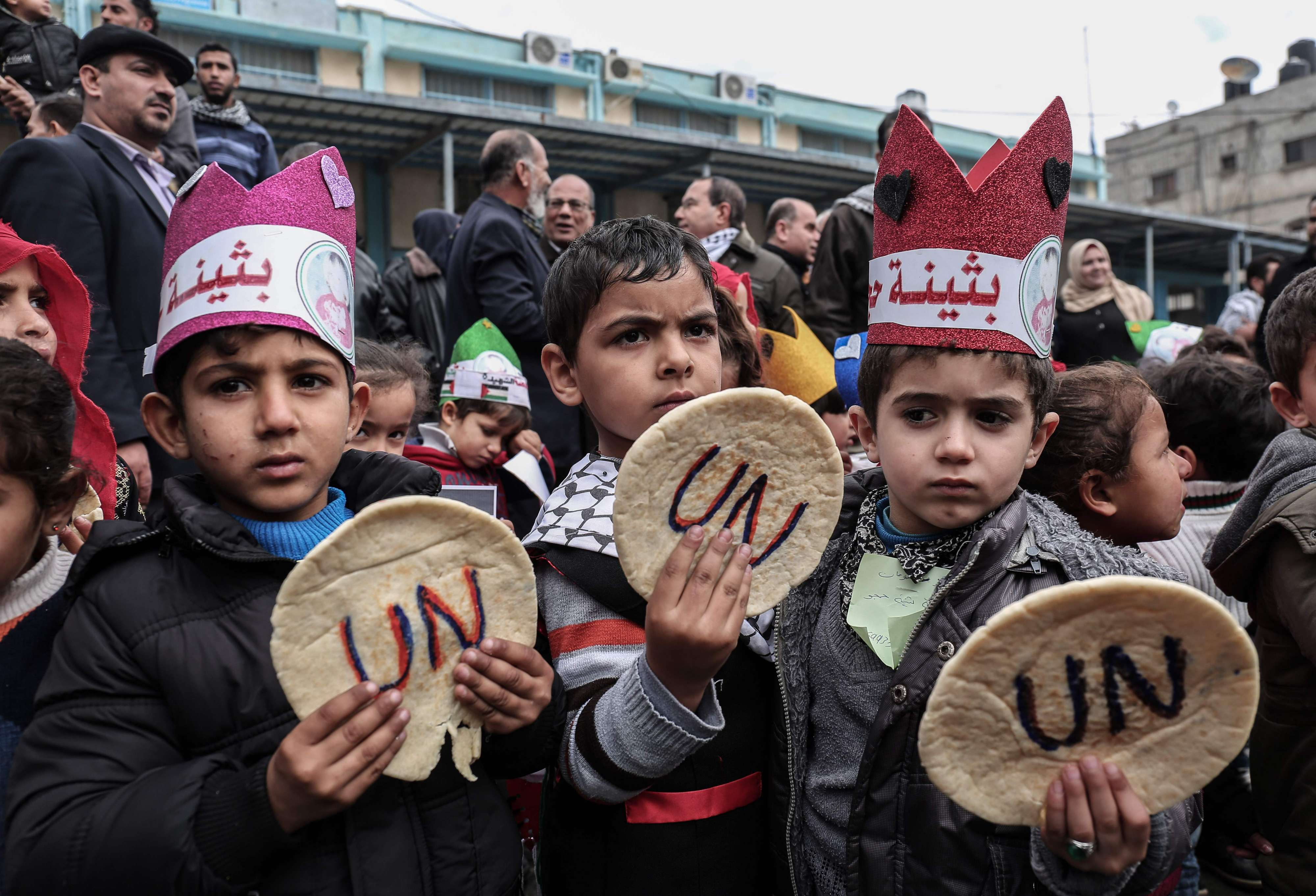 Palestinian children hold bread patties during a protest against US aid cuts outside the United Nations' offices in Gaza Strip, on January 28. (AFP)
