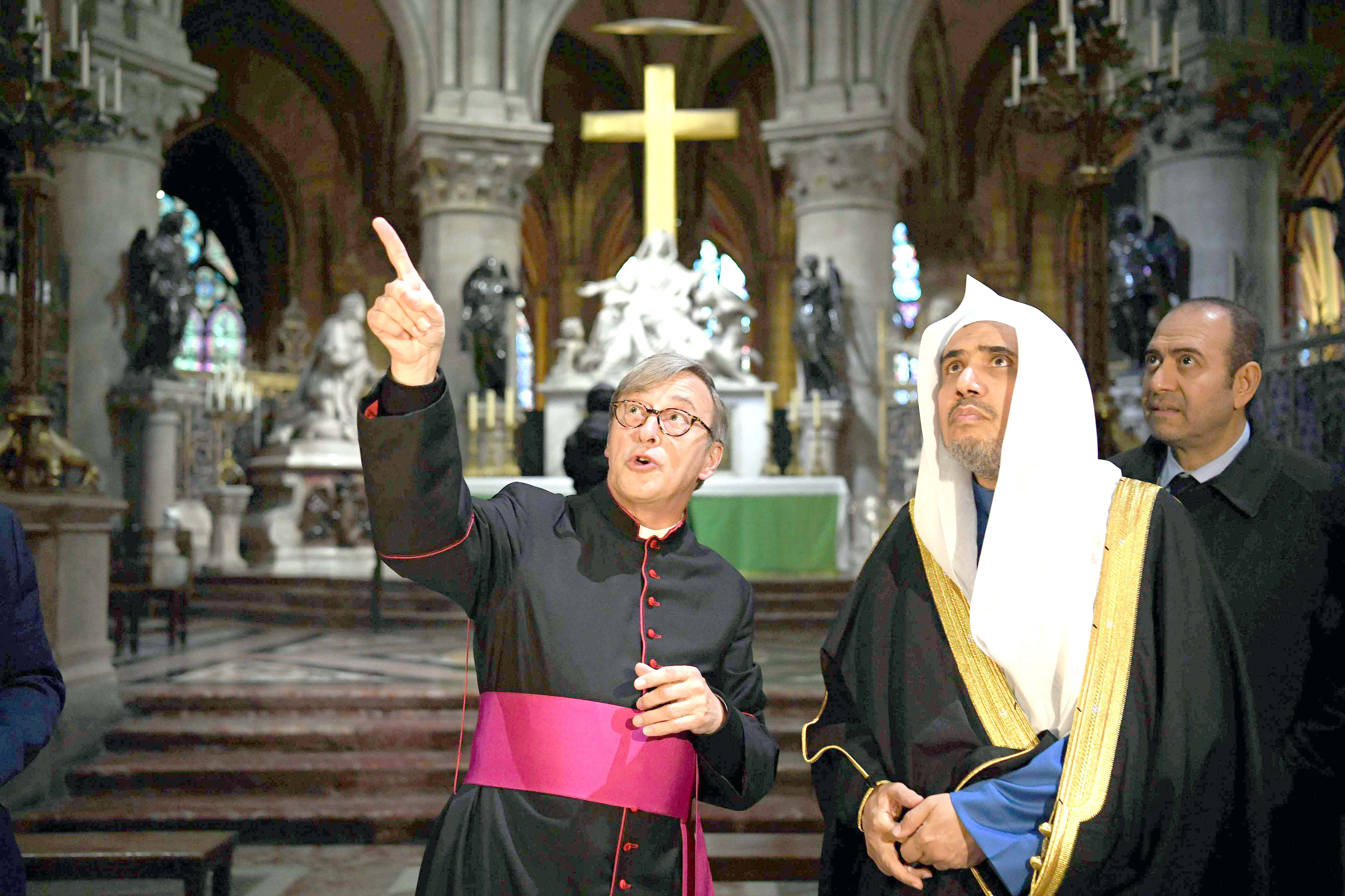Muslim World League Secretary-General Mohammad bin Abdul Karim al-Issa (2nd R) listens to the Rector of the Notre-Dame de Paris Cathedral Patrick Chauvet (L) during a visit to the cathedral, last November.  (AFP)