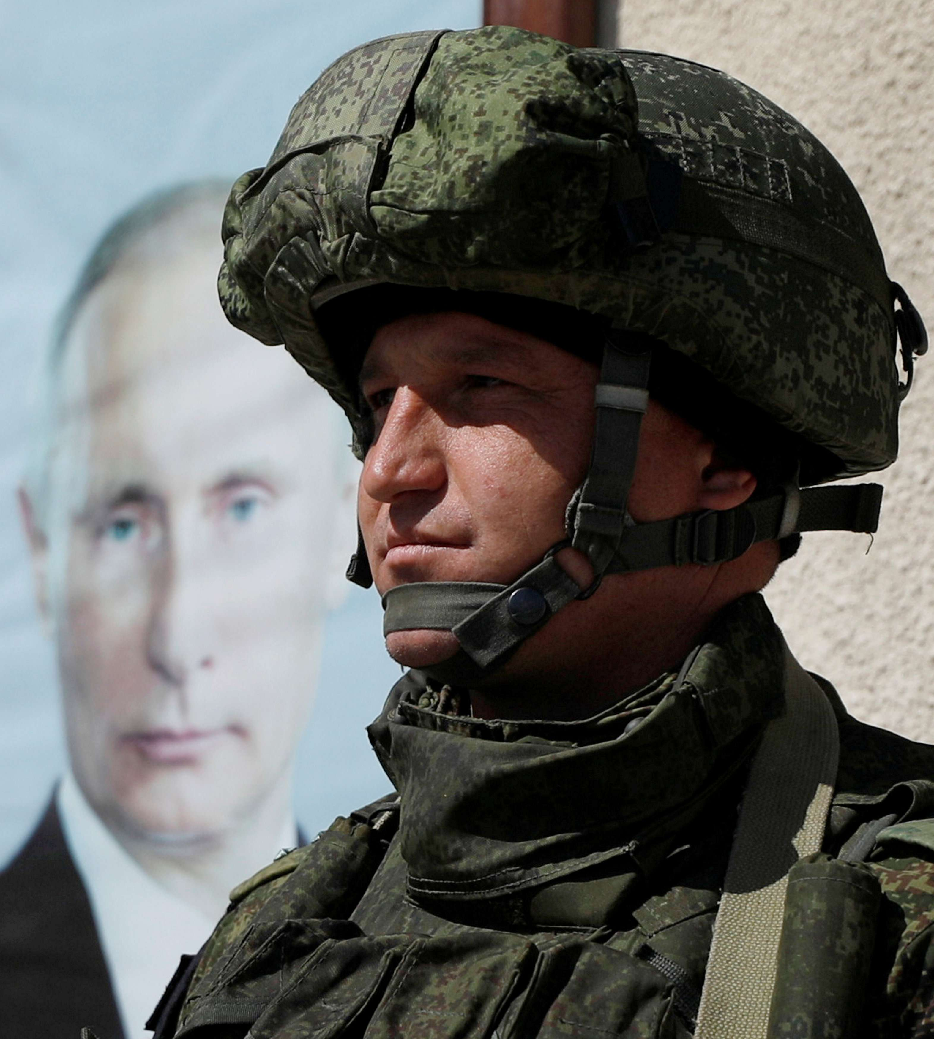 A Russian soldier stands near a poster of Russian President Vladimir Putin at Wafideen camp in Damascus, Syria, on March 2, 2018.  (Reuters)