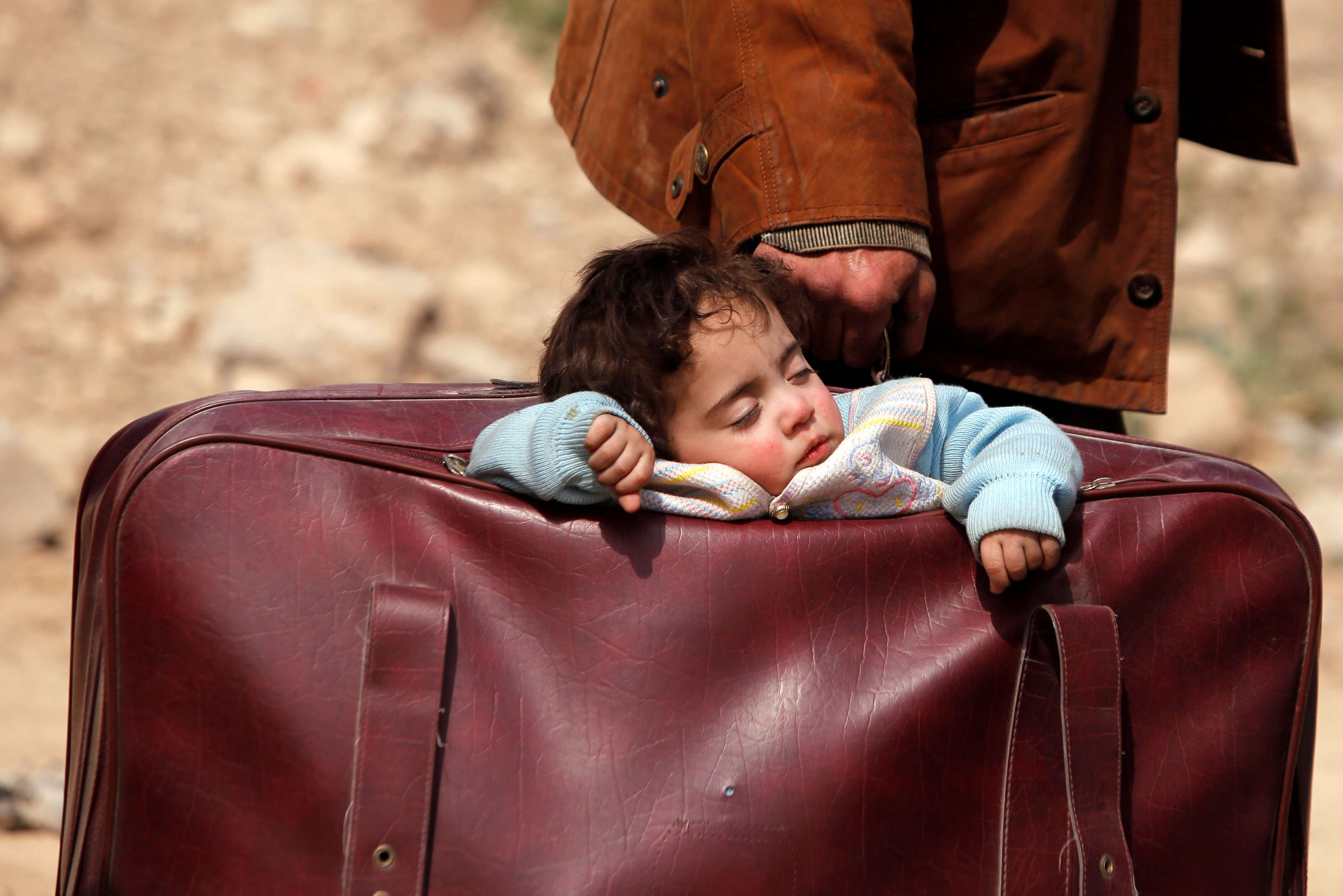 A child sleeps in a bag in the village of Beit Sawa in eastern Ghouta, on March 15. (Reuters)
