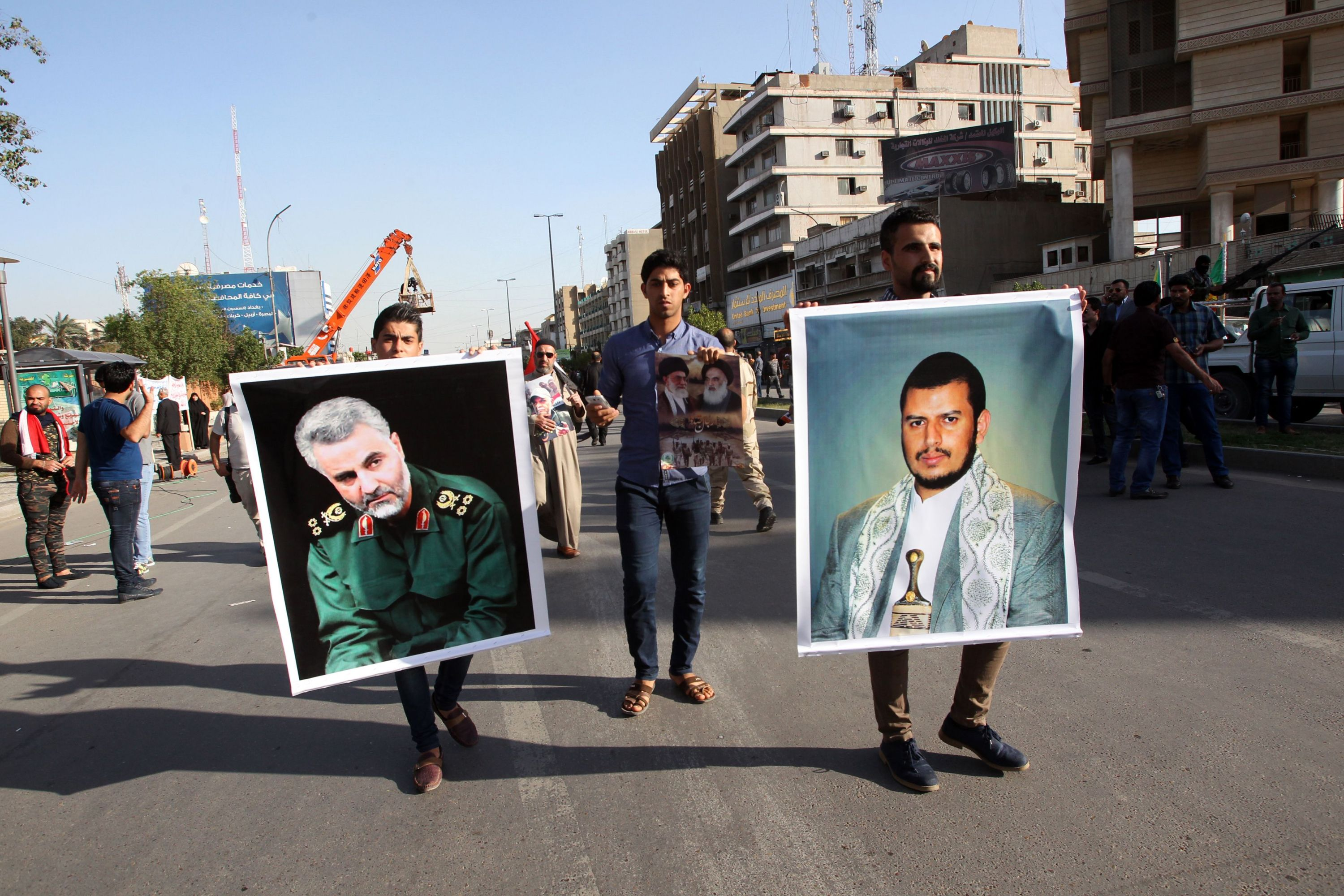 Many faces of the problem. Iraqis hold portraits of Houthi rebels' leader Abdulmalik al-Houthi (R) and Commander of Iran's al-Quds Force Qassem Soleimani during a rally in Baghdad. (AFP)
