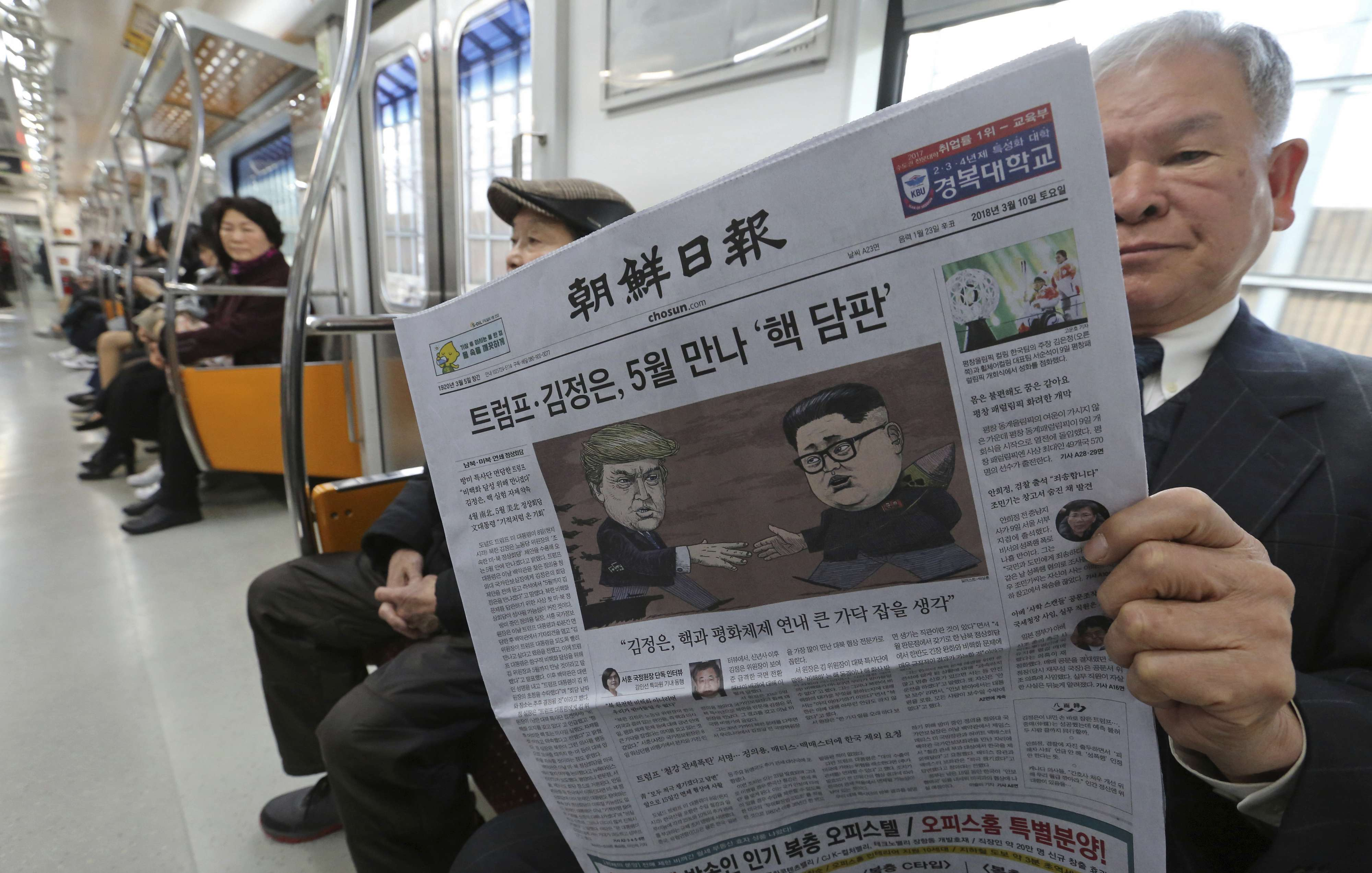 A passenger on a subway train in Seoul on March 10 reads a newspaper with a headline of a planned summit meeting between North Korean leader Kim Jong-un and US President Donald Trump. 		(AP)