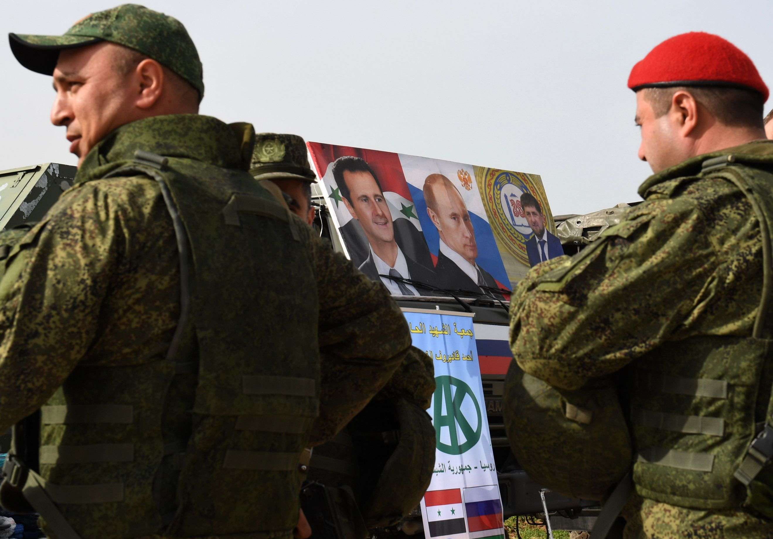 Russian soldiers stand near a vehicle bearing images of Syrian, Russian and Chechnyan leaders in the area of Abu al-Duhur, on March 4. (AFP)