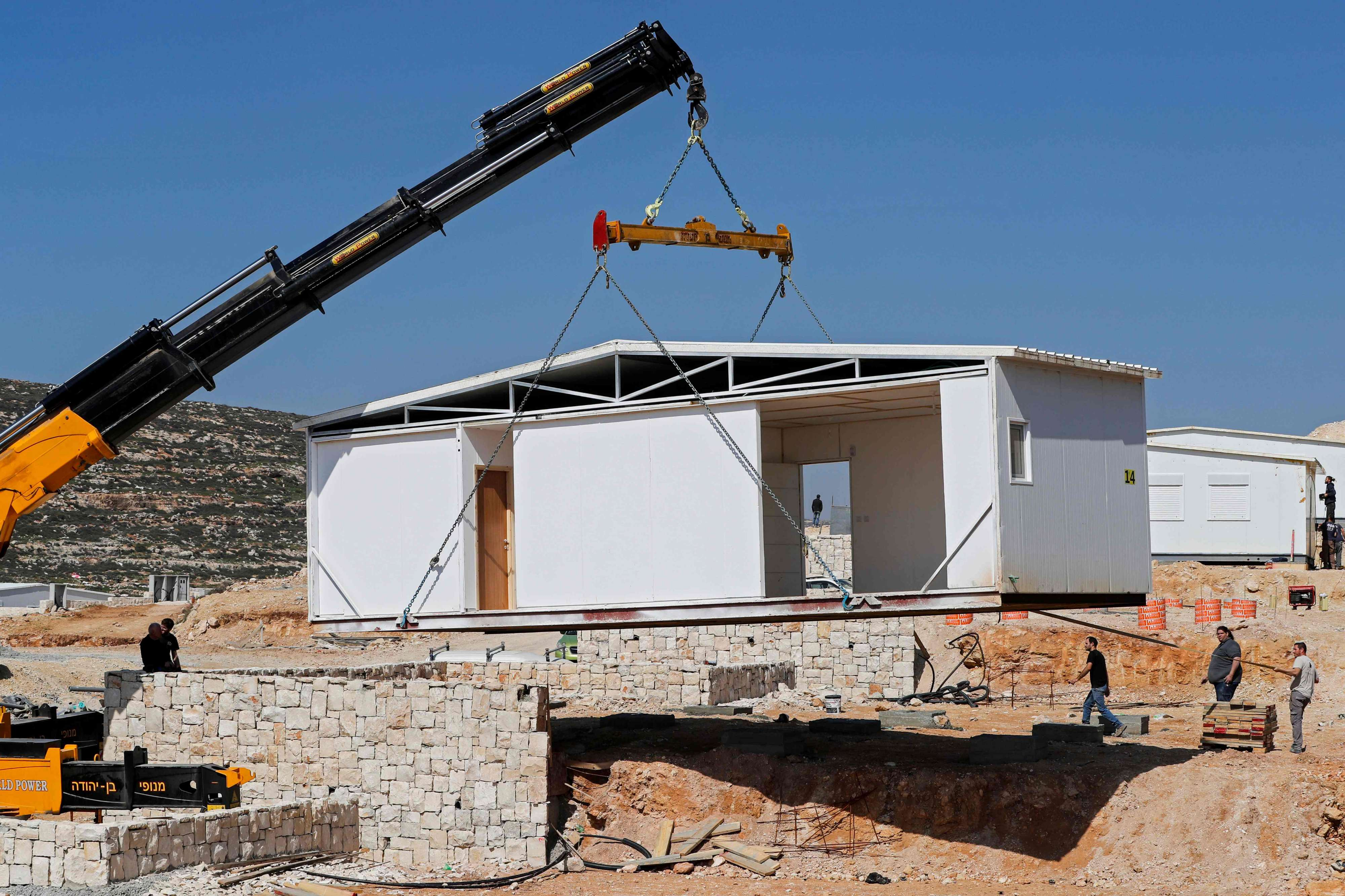 A construction crane installs a new mobile homes in Amichai near the settlement of Shiloh in the Israeli-occupied West Bank, on February 21.