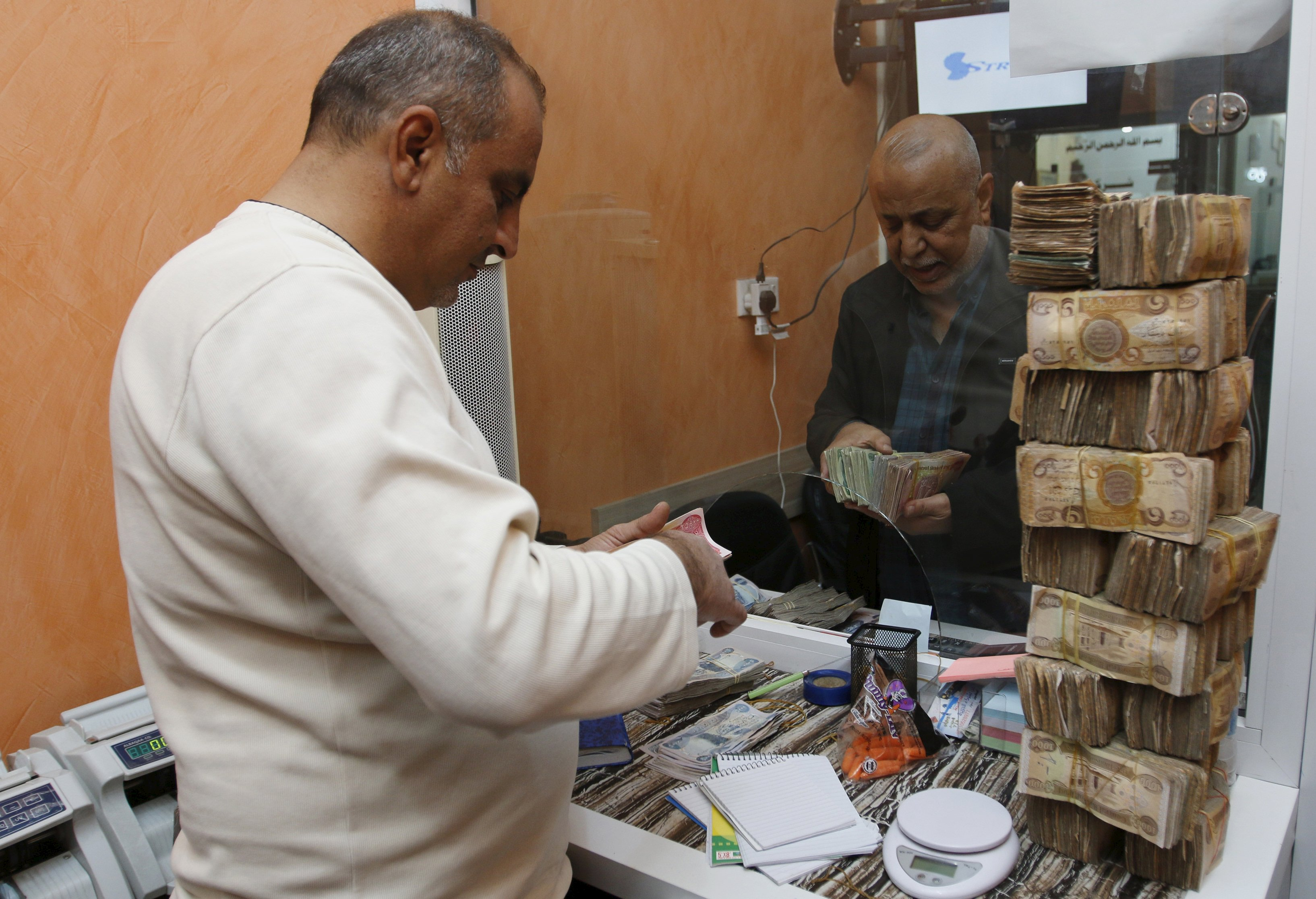 A man (R) changes US dollars to Iraqi dinars at a currency exchange shop in Baghdad. (Reuters)