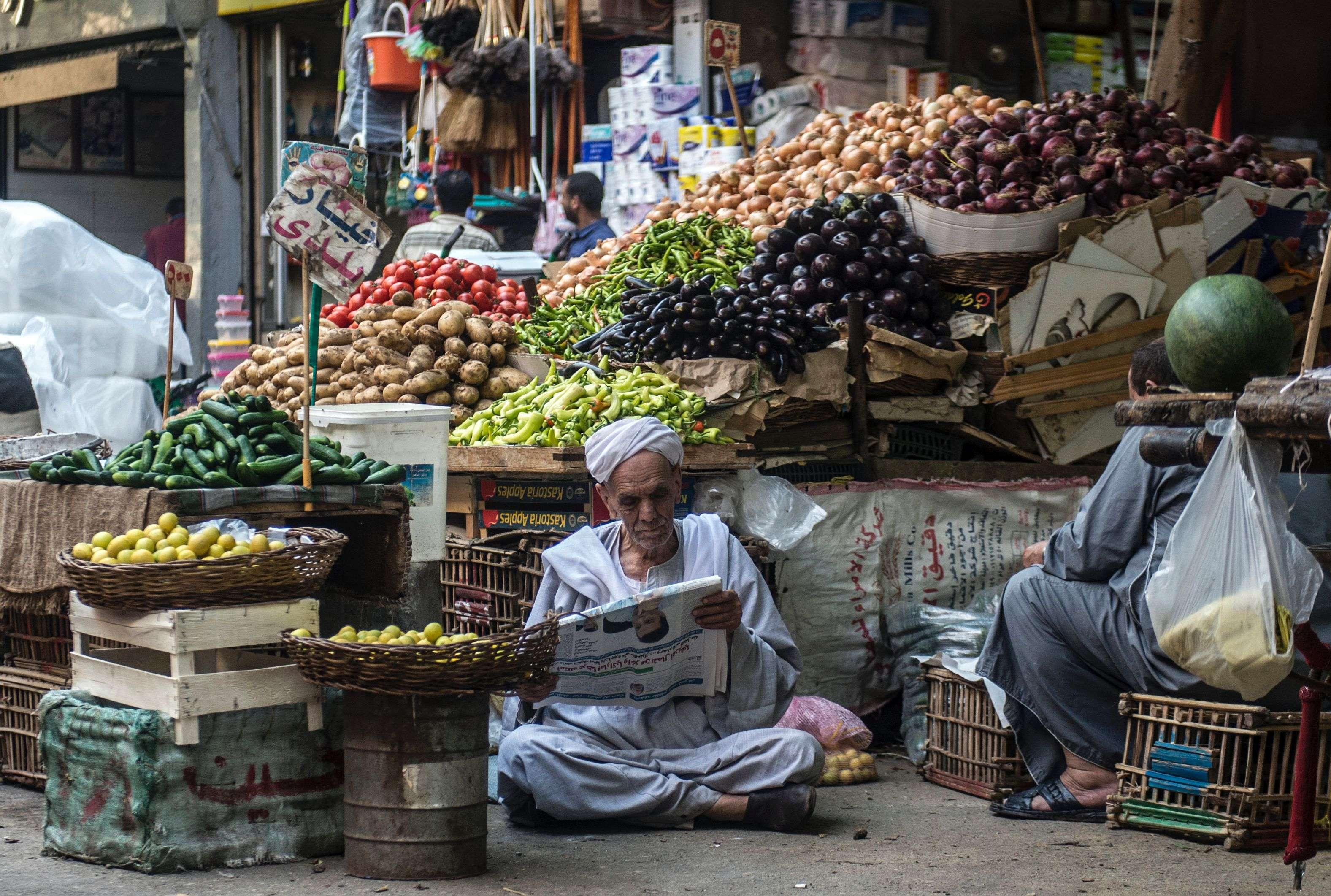 An Egyptian vendor reads the newspaper outside his fruit and vegetable stand in Cairo. (AFP)
