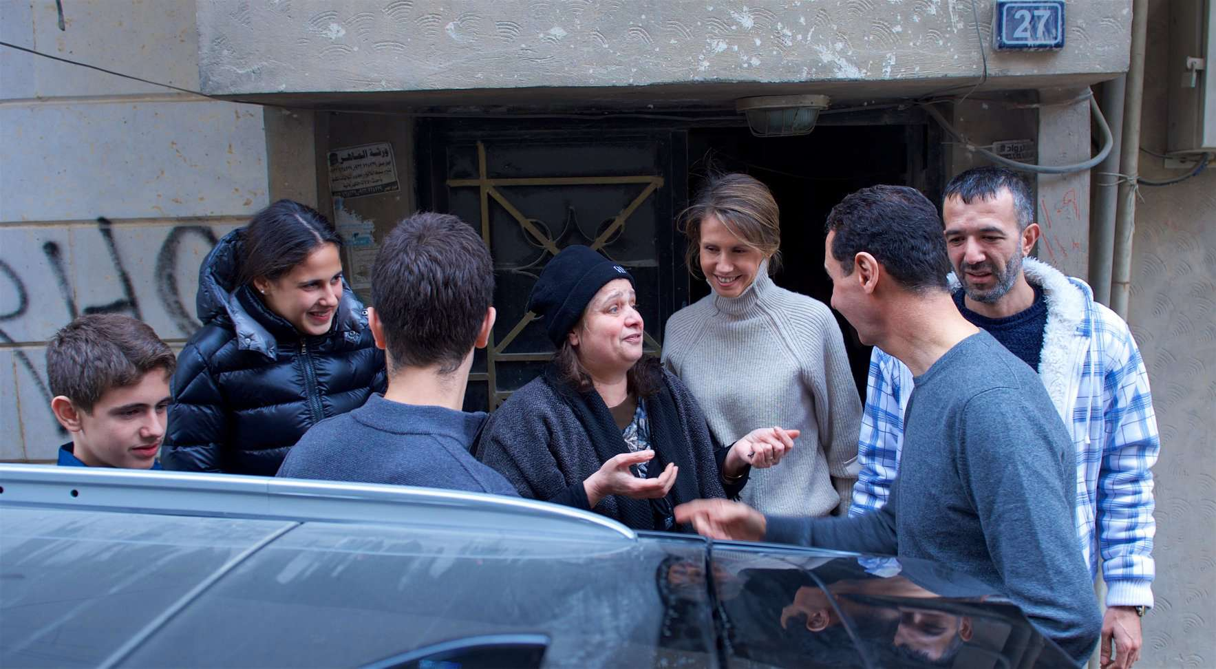 Syrian President Bashar Assad (R), his wife Asma (3-R), his daughter Zein(2-L), and sons Hafez (3-L) and Karim (L) speak to locals during a visit to Homs, last December. (Syrian Presidency )