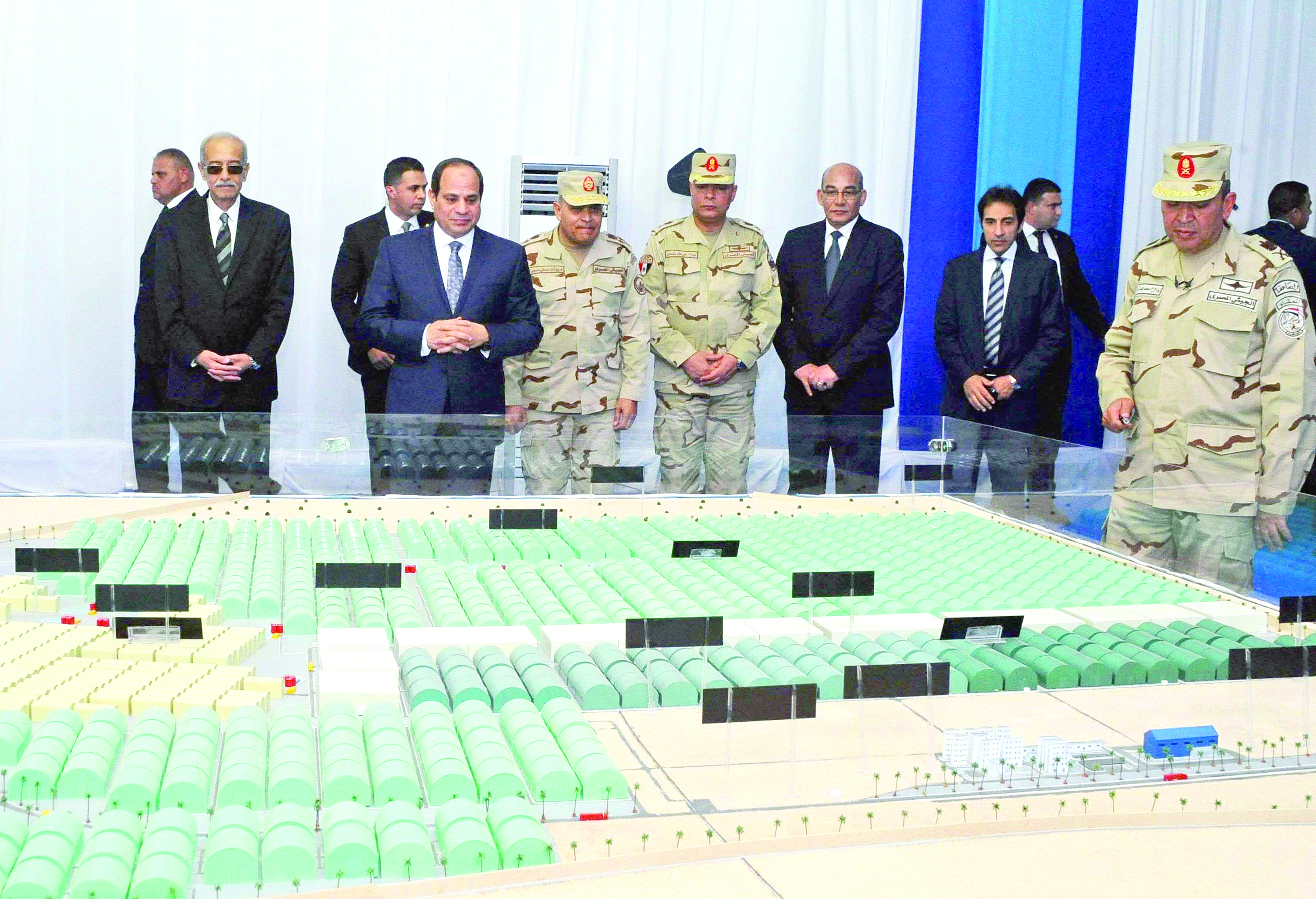 Egyptian President Abdel Fattah al-Sisi (2nd-L) looks at model diagrams of greenhouses during the inauguration of an agricultural project at Mohamed Naguib military base in al-Hammam region, last February. (Egyptian Presidency)