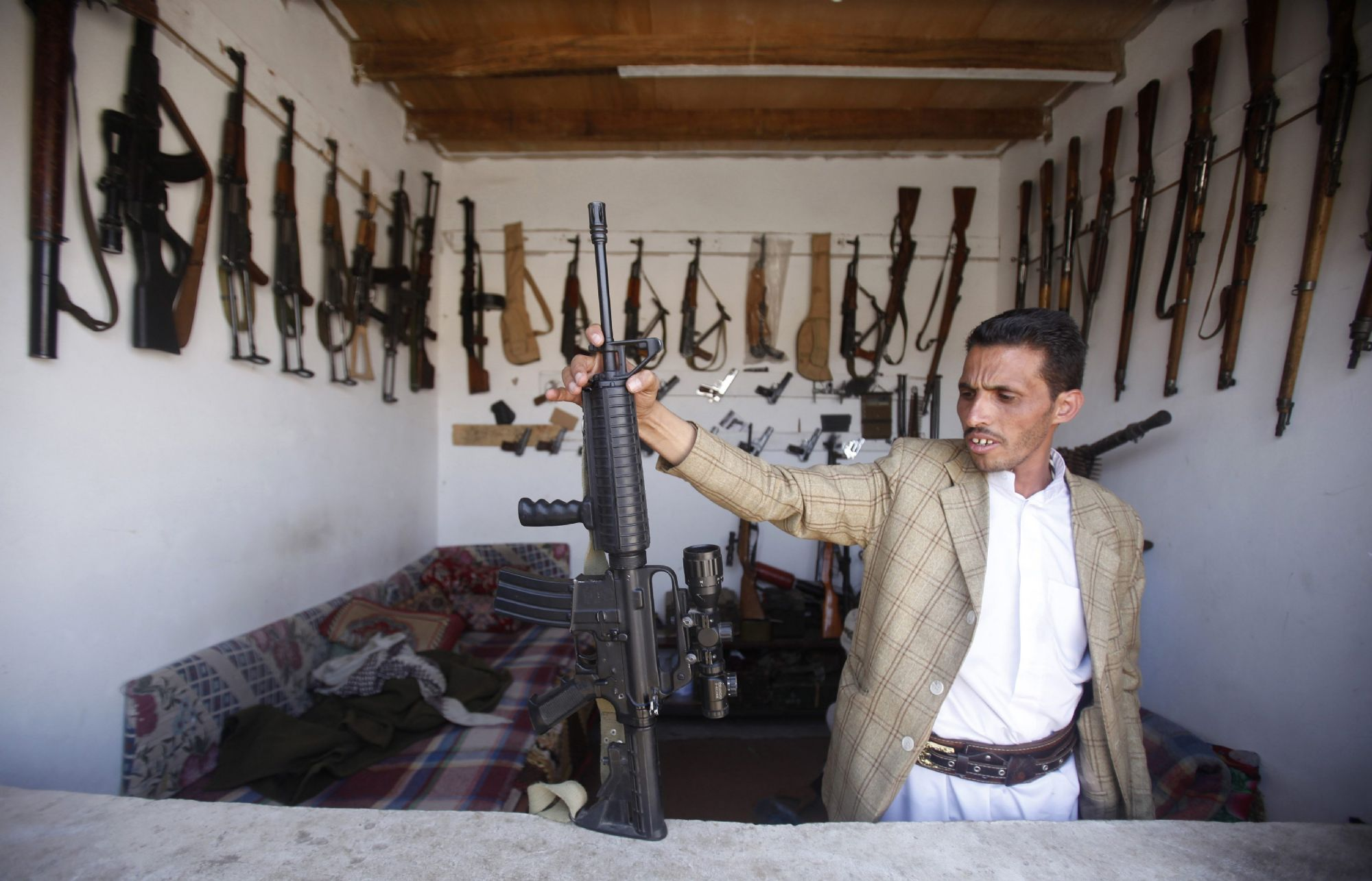 An arms dealer displays a rifle in his shop in Jihana, about 30km east of Sanaa. (Reuters)