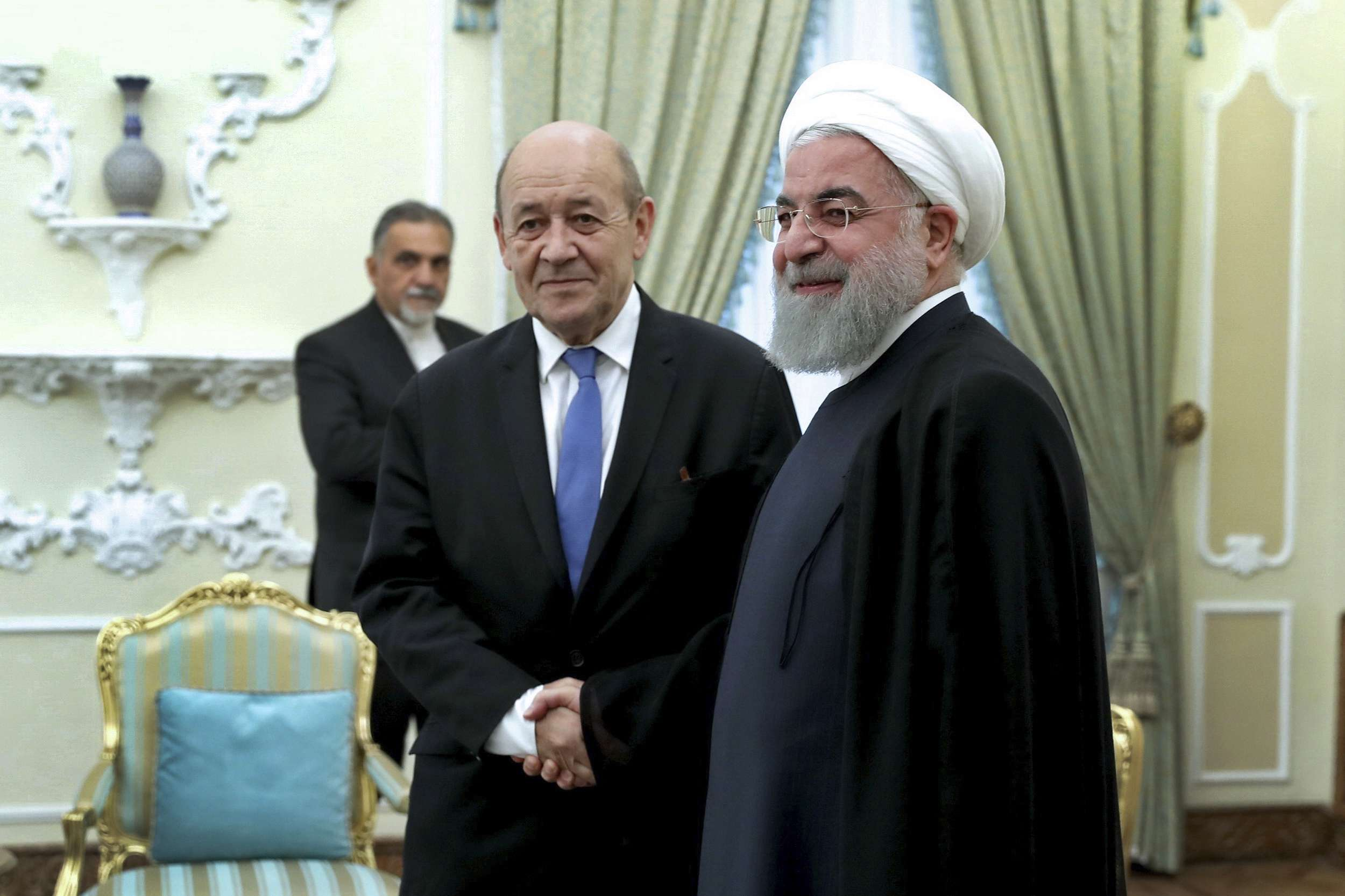 Iranian President Hassan Rohani (R) welcomes French Foreign Minister Jean-Yves Le Drian at the start of their meeting in Tehran, on March 5.     (Iranian Presidency Office)