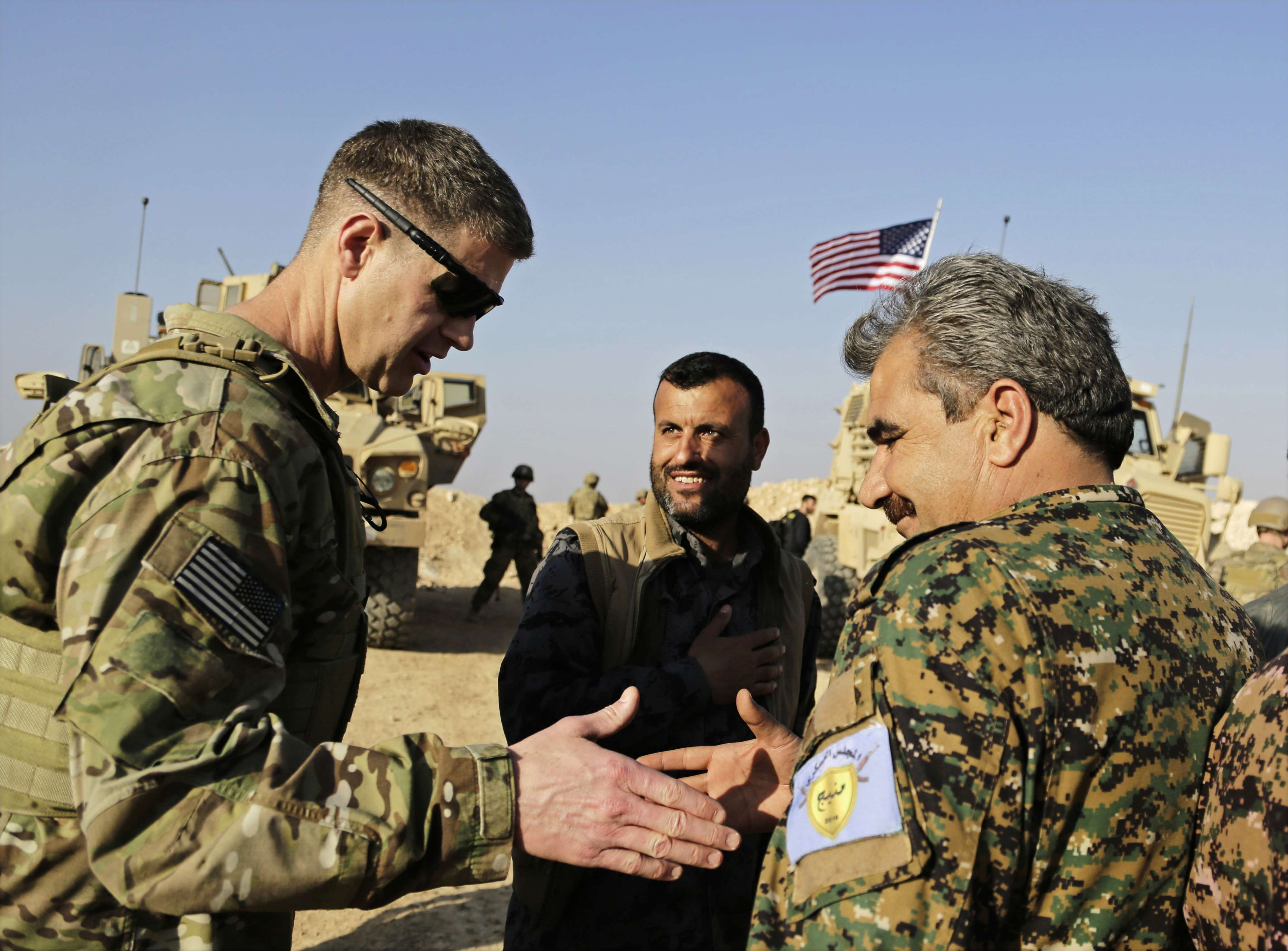 US Army Major-General Jamie Jarrard (L) and Manbij Military Council Commander Muhammed Abu Adeel shake hands during a visit to a small outpost near Manbij, last February. (AP)
