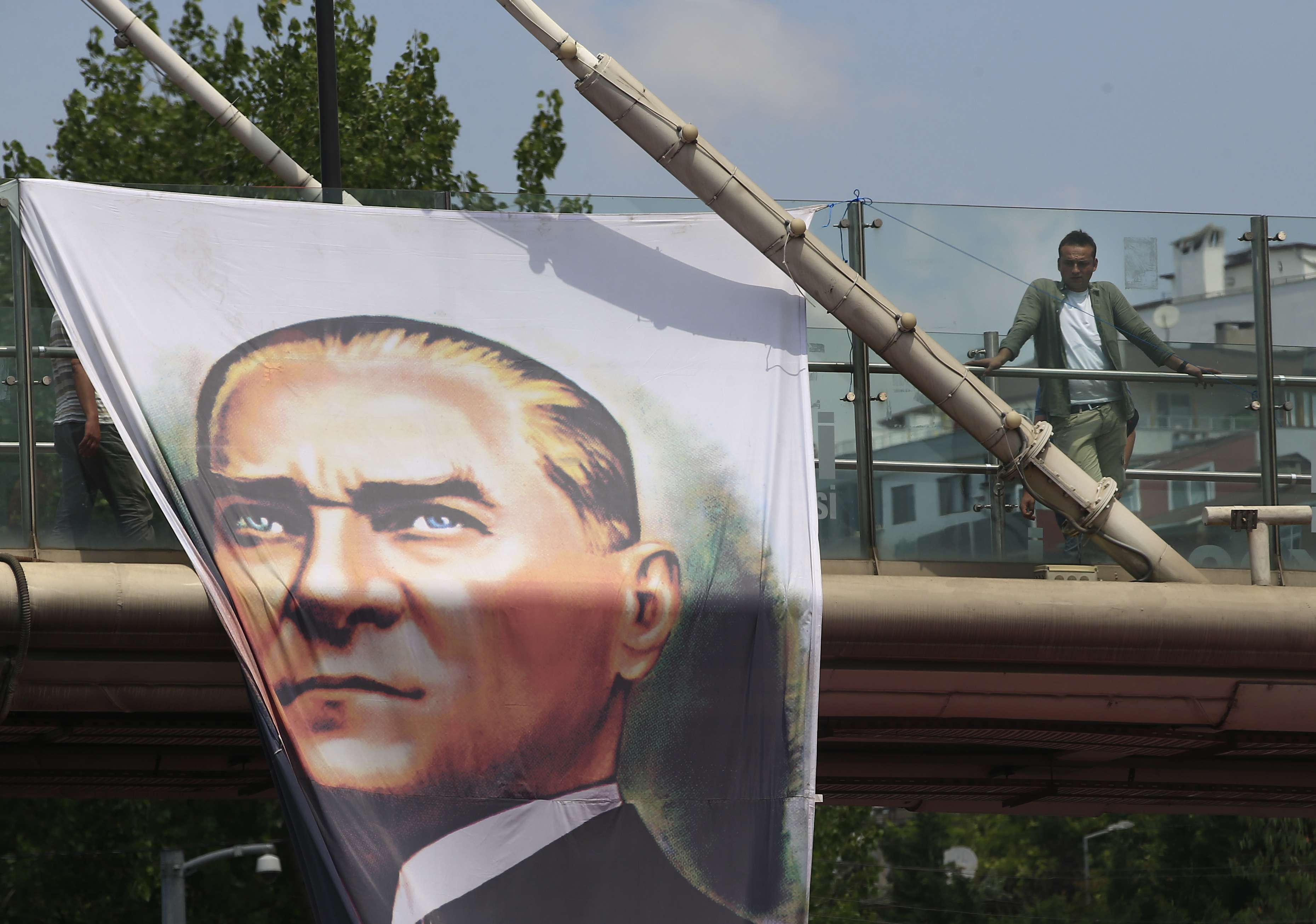 A poster of modern Turkey's founder Mustafa Kemal Ataturk decorates a bridge as a plain clothes police officer keeps a watchful eye in Istanbul. (AP)