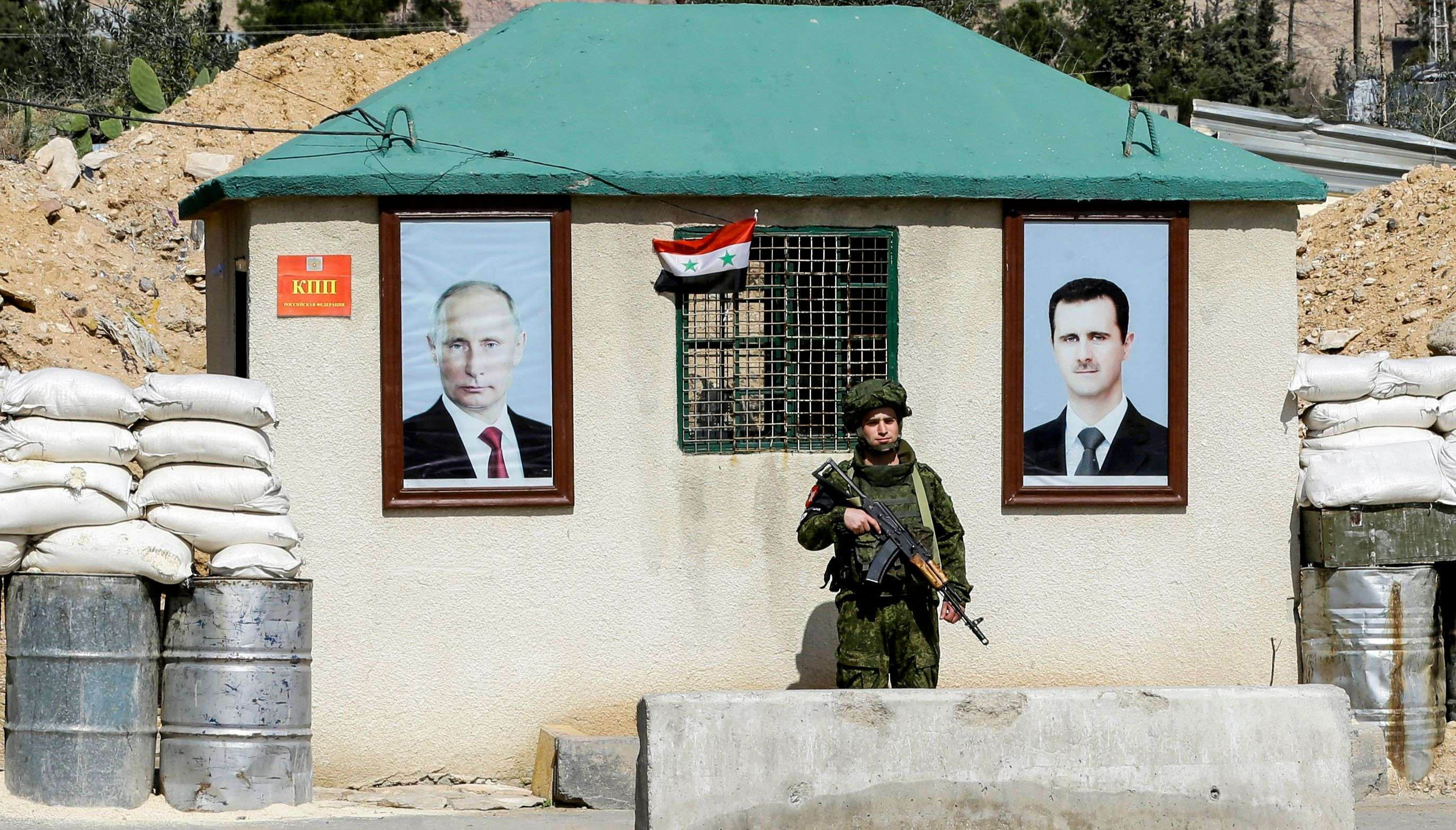 A Russian army soldier standing guard between the portraits of Syrian President Bashar al-Assad (R) and Russian President Vladimir Putin, outside at a checkpoint on the outskirts of Damascus, on March 1. (AFP)