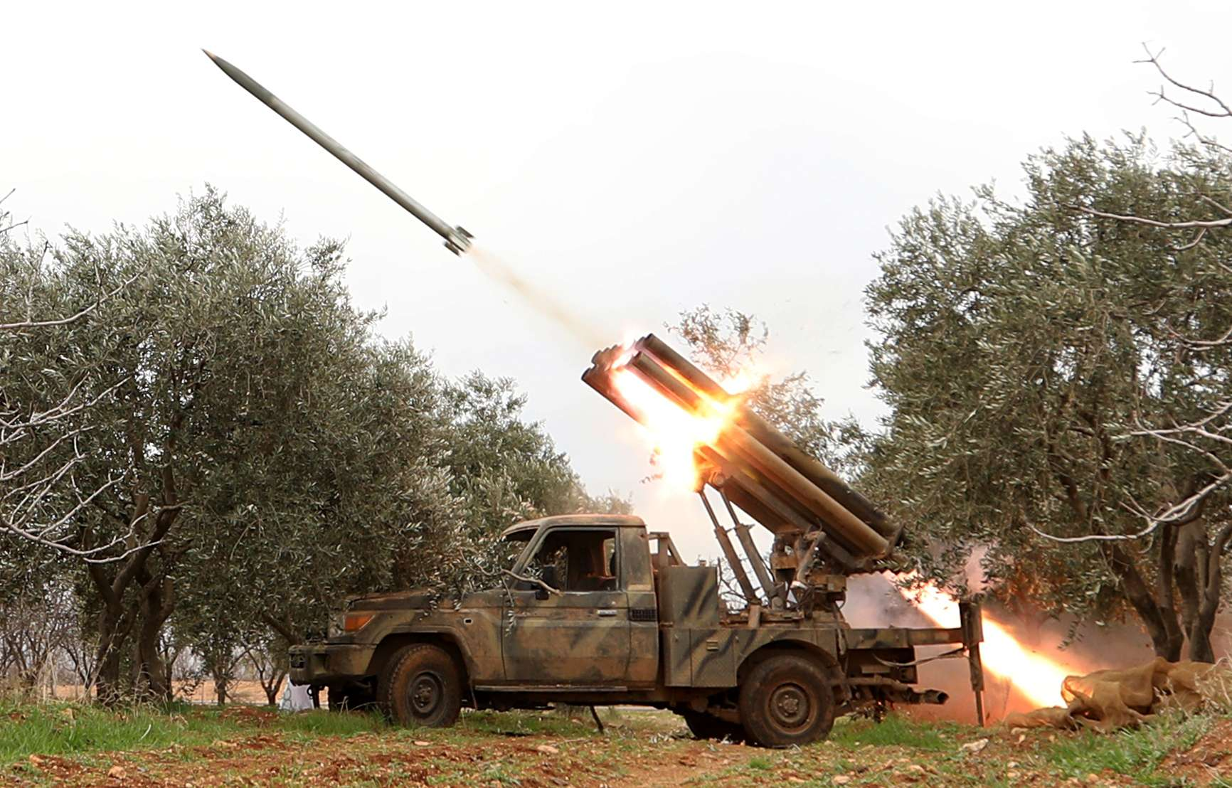 Fighters from the Hayat Tahrir al-Sham fire missiles from a village near al-Tabanah in Syria's Idlib province, in January. (AFP)