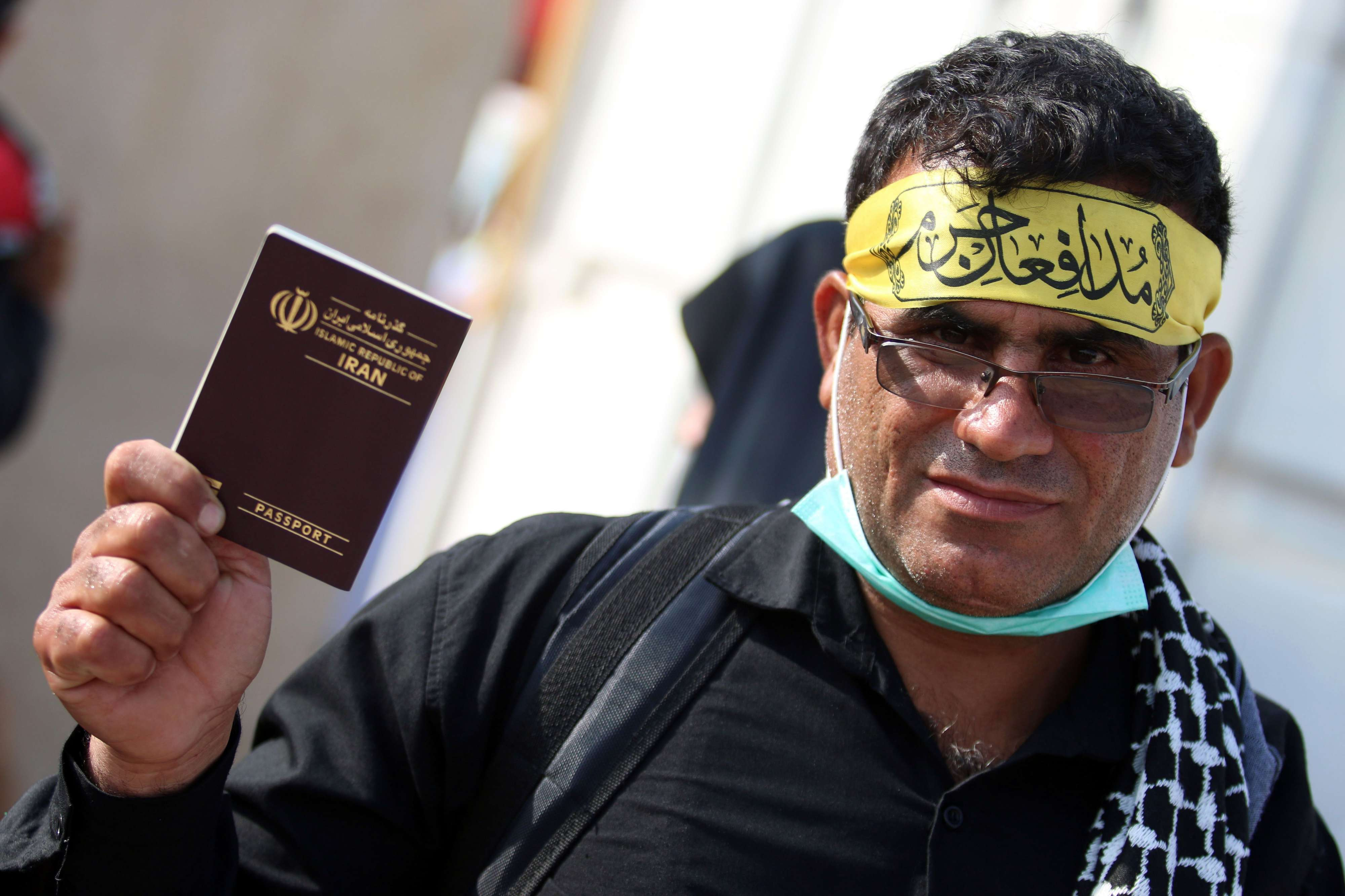 An Iranian pilgrim flashes his passport while passing through a border crossing in the Iraqi city of Basra. (AFP)