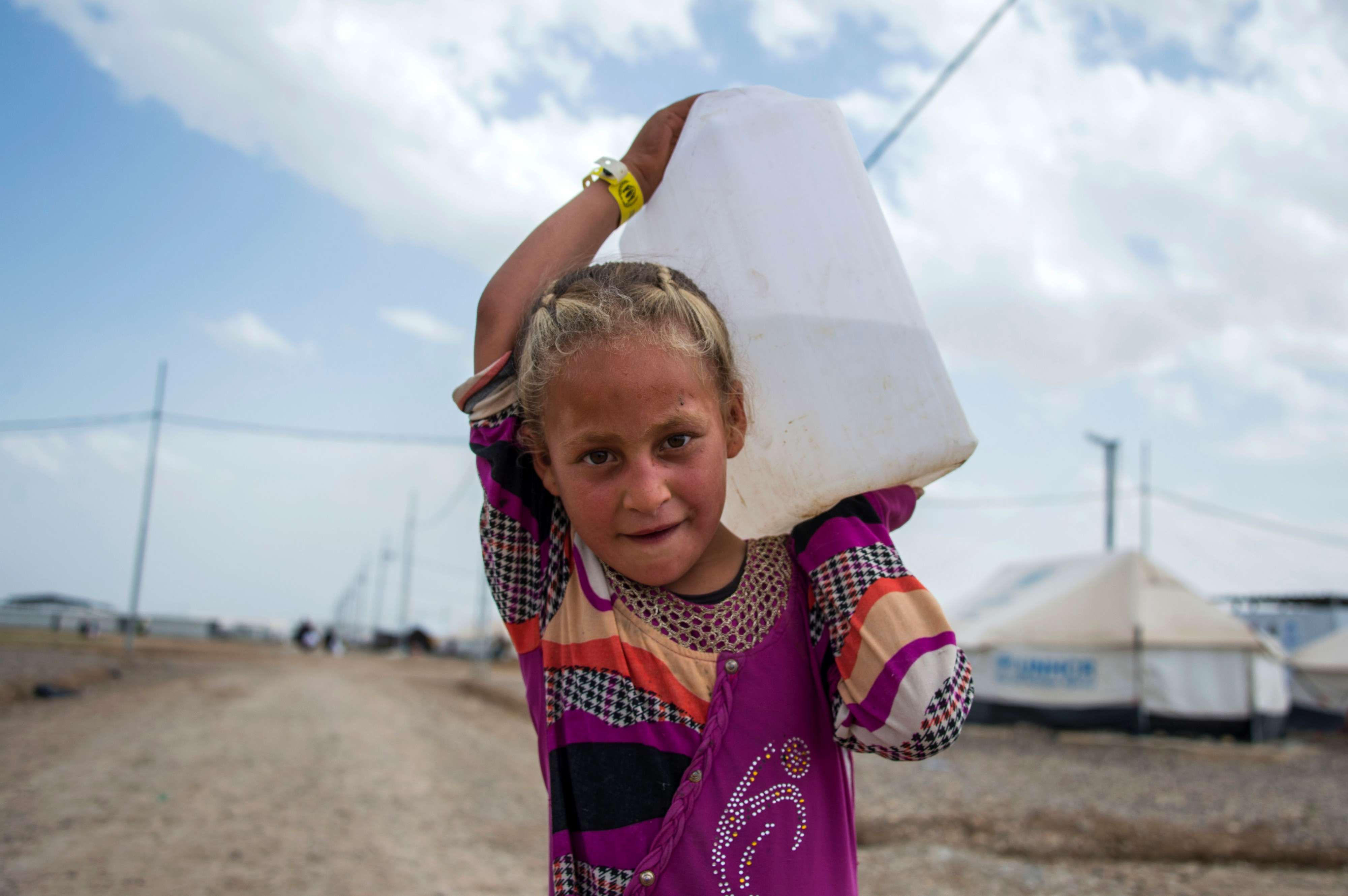 An Iraqi girl carries water at a camp for internally displaced people in Hammam al-Alil, last year. (AFP)