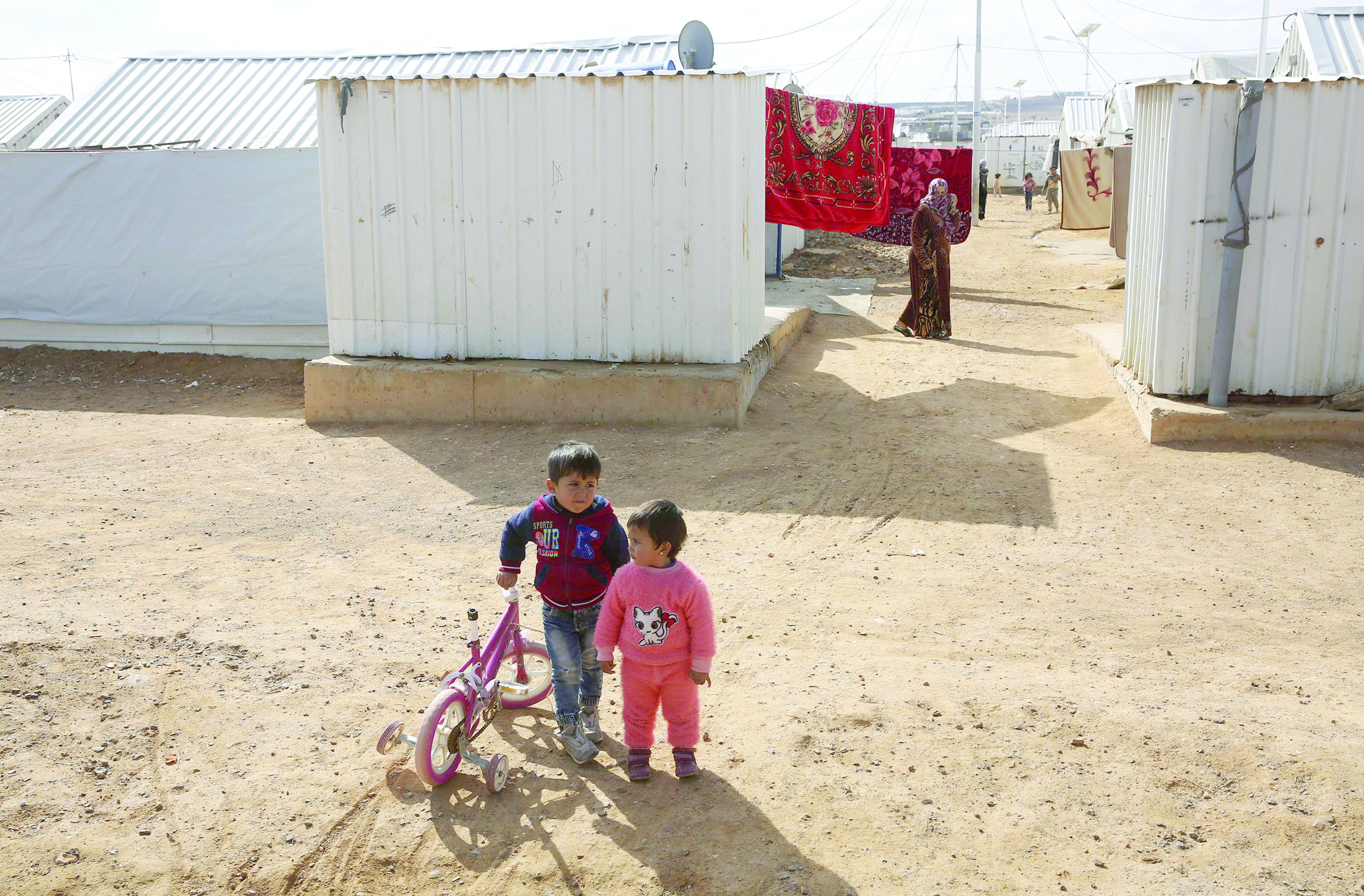Two children play with a bicycle at the Azraq camp for Syrian refugees in Jordan. (AP)