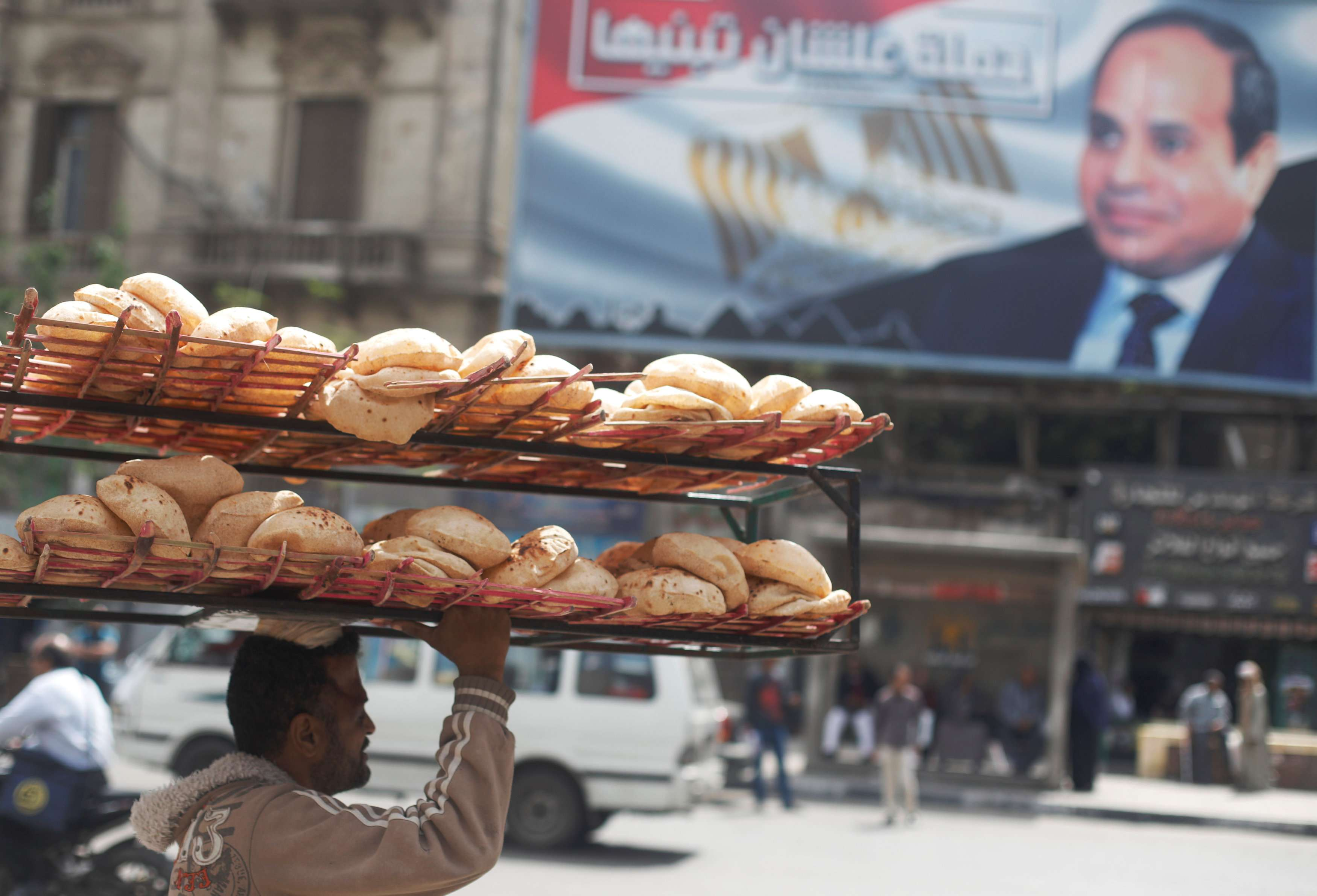 "A man carries bread on his head near a banner for Egyptian President Abdel Fattah al-Sisi from the campaign titled ""Alashan Tabneeha"" (""So You Can Build It"") after election results in Cairo, on April 3. (Reuters)"