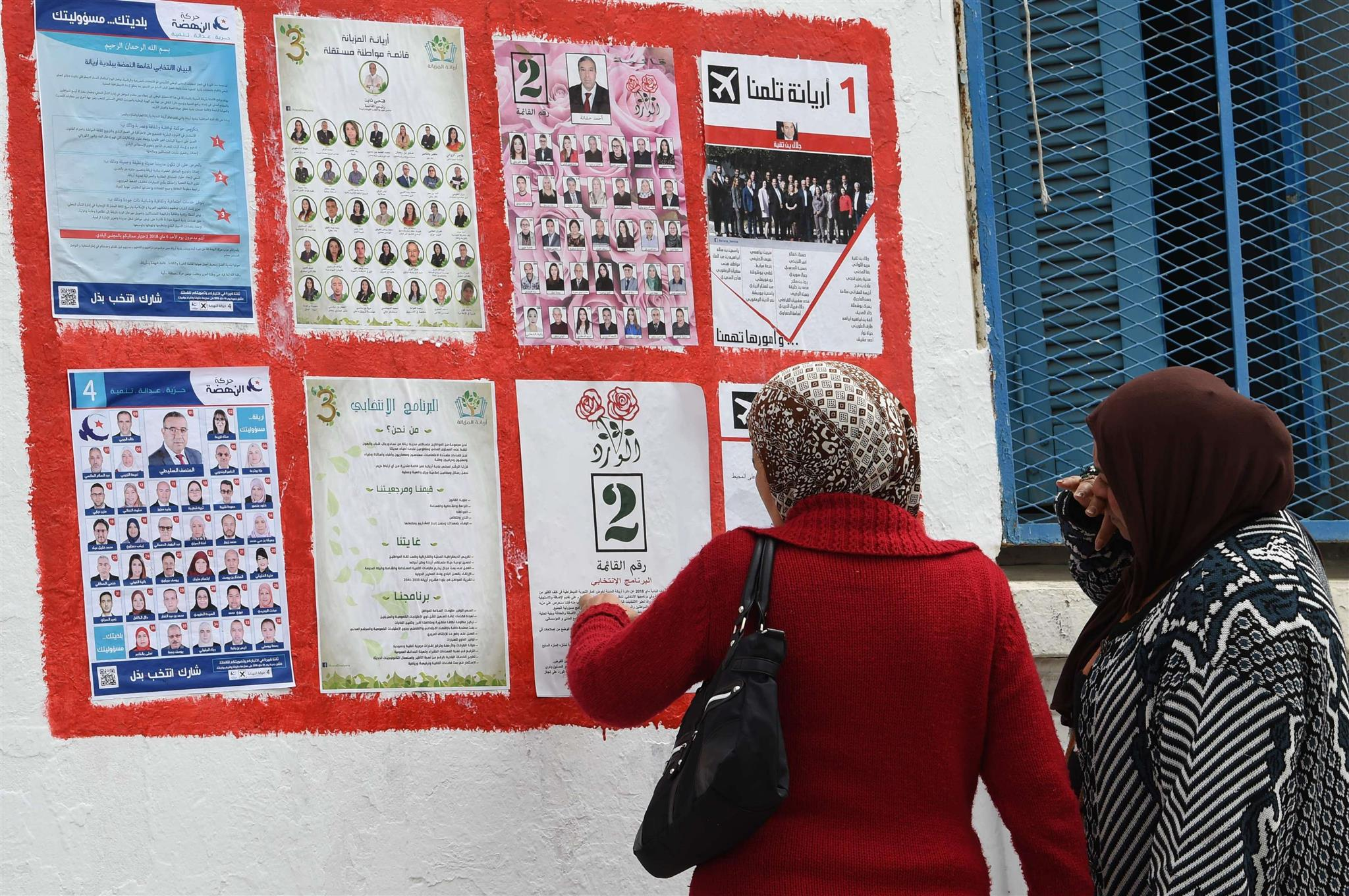 Tunisians look at lists of candidates for the upcoming municipal elections in the city of Ariana, on April 14. (AFP)