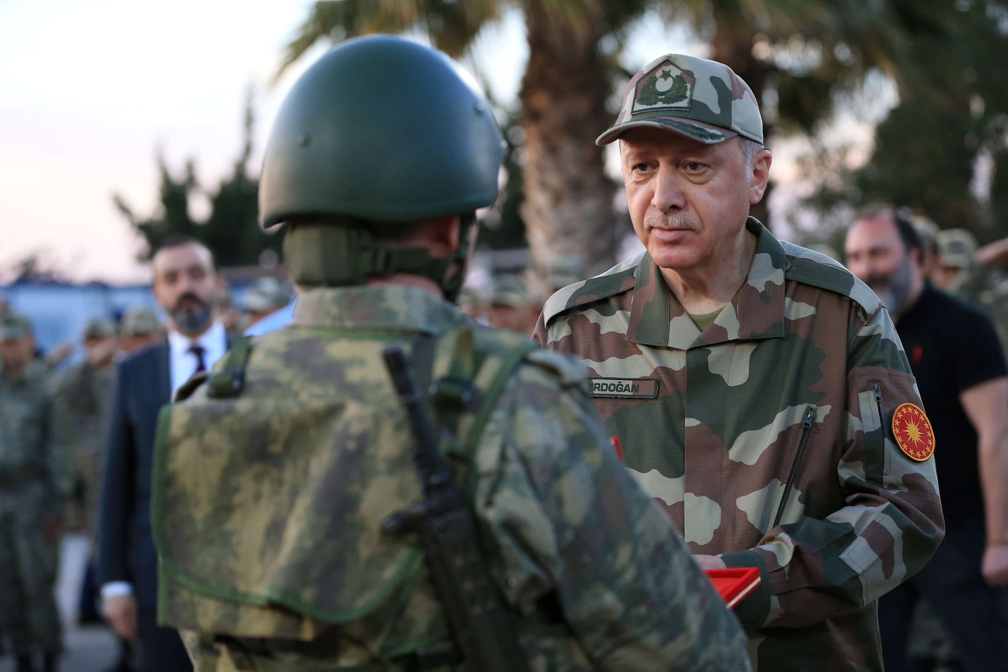 In the spotlight. Turkish President Recep Tayyip Erdogan, wearing a military uniform, arrives at Ogulpinar military post on the Turkish-Syrian border, on April 1. (Reuters)