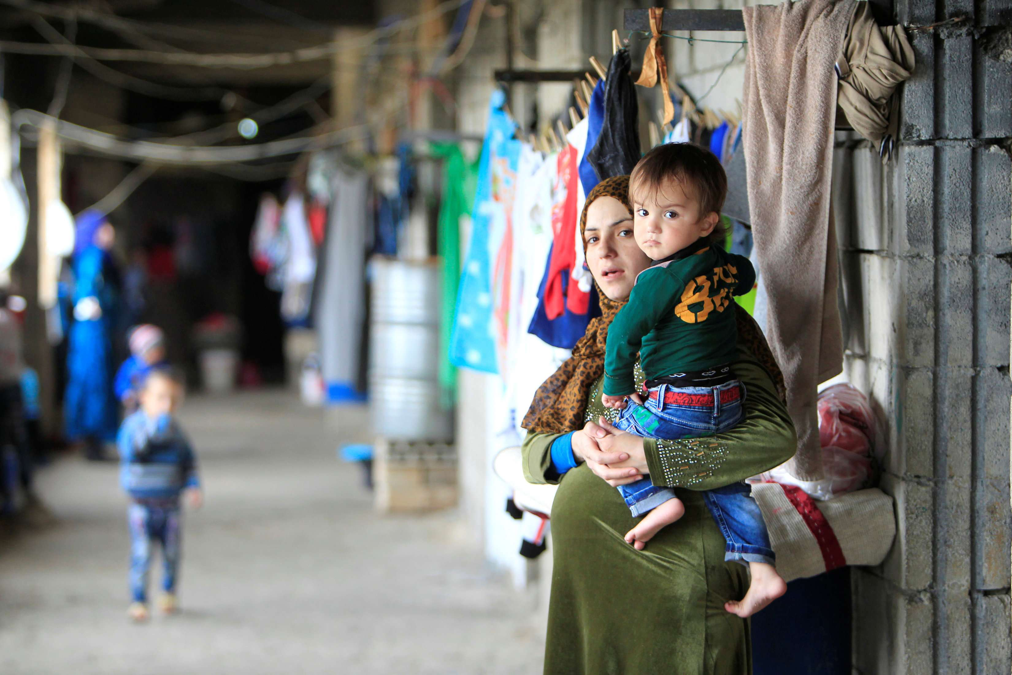 A pregnant Syrian woman carries her child at a  compound housing Syrian refugees in Sidon in southern Lebanon. (Reuters)