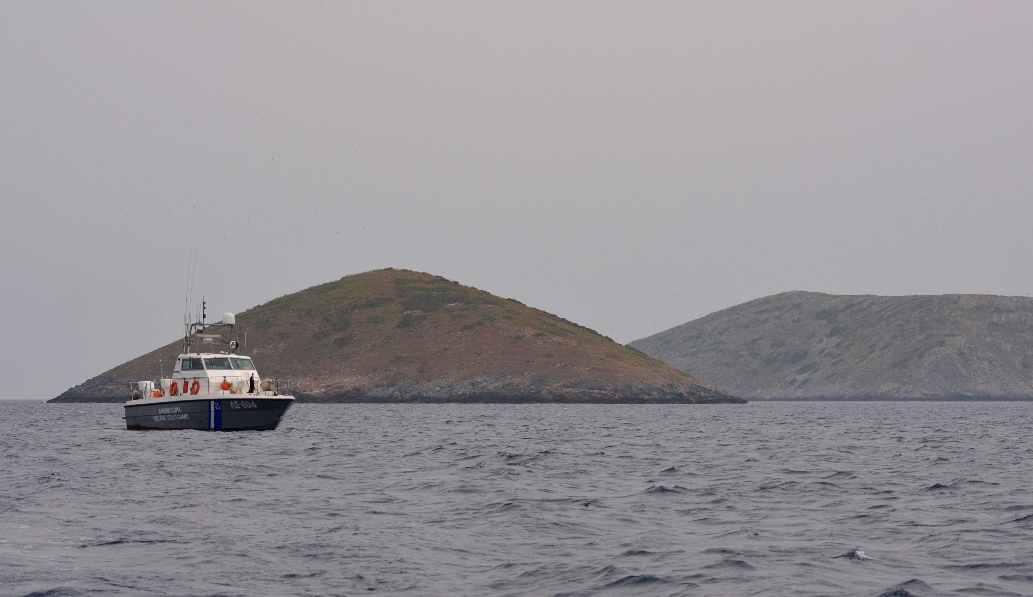 A Greek Coast Guard vessel sails next to the Mikros Anthropofas (L) and Megalos Anthropofas (R) islets , on April 16. (Reuters)