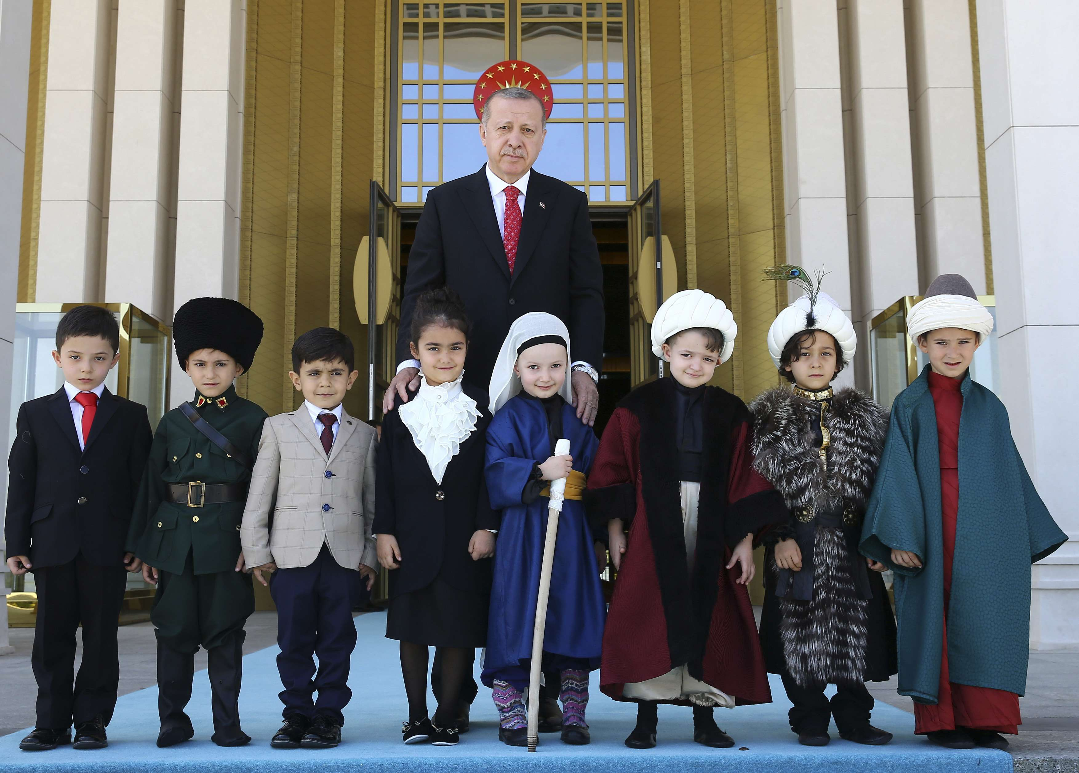 One-man rule. Turkish President Recep Tayyip Erdogan (C) poses for photographs with pupils, dressed in traditional costume, during a school visit at the Presidential Palace. (AP)