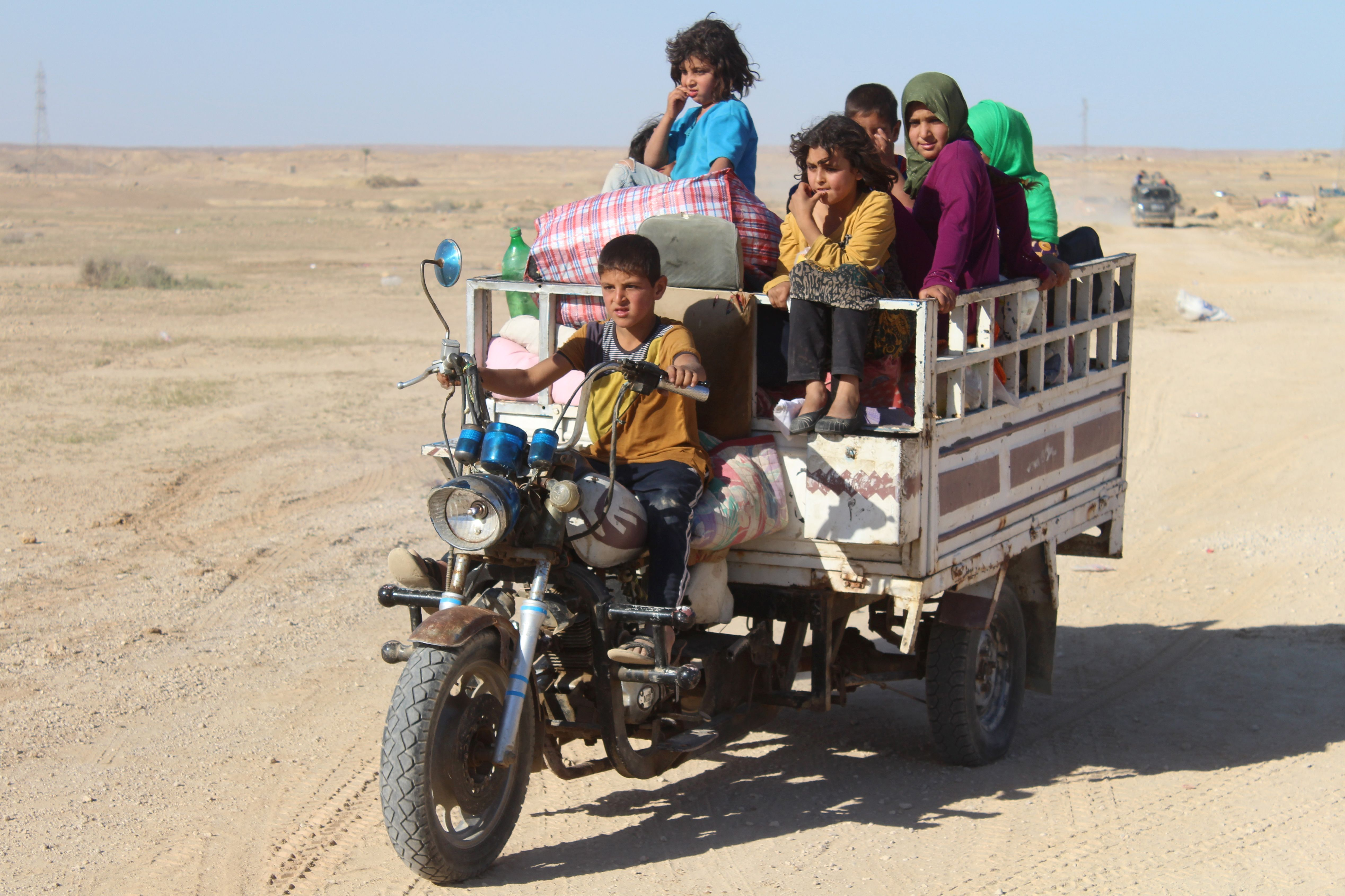 Iraqi children sit in a three-wheel motorcycle near the town of Heet in Iraq's Anbar  province.       (AFP)