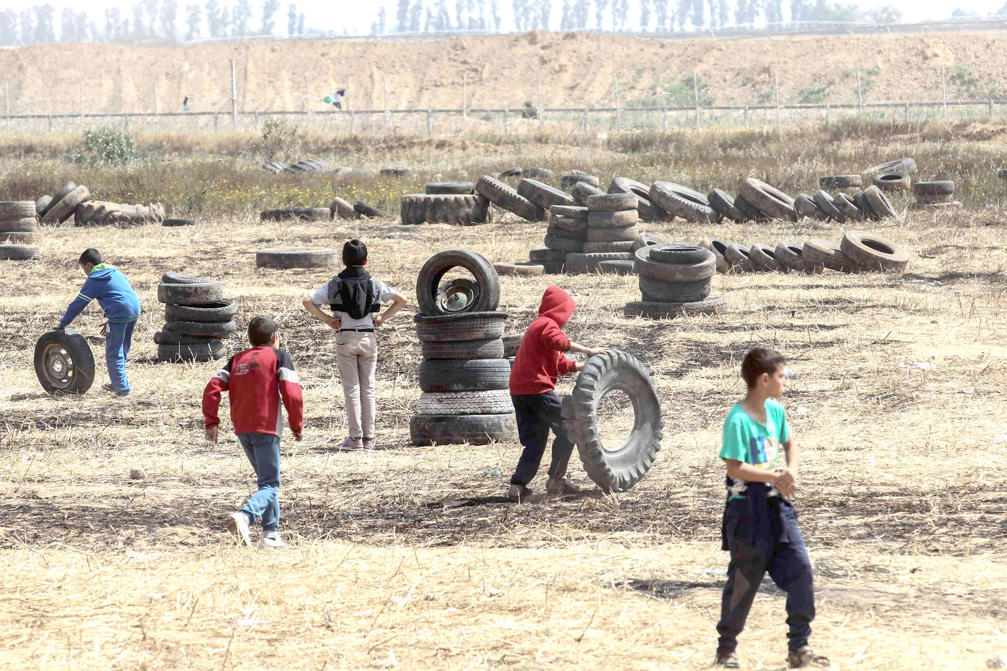 Palestinian children collect tyres before burning them to protect themselves from shots by Israeli soldiers near the Israel-Gaza border. (AFP)