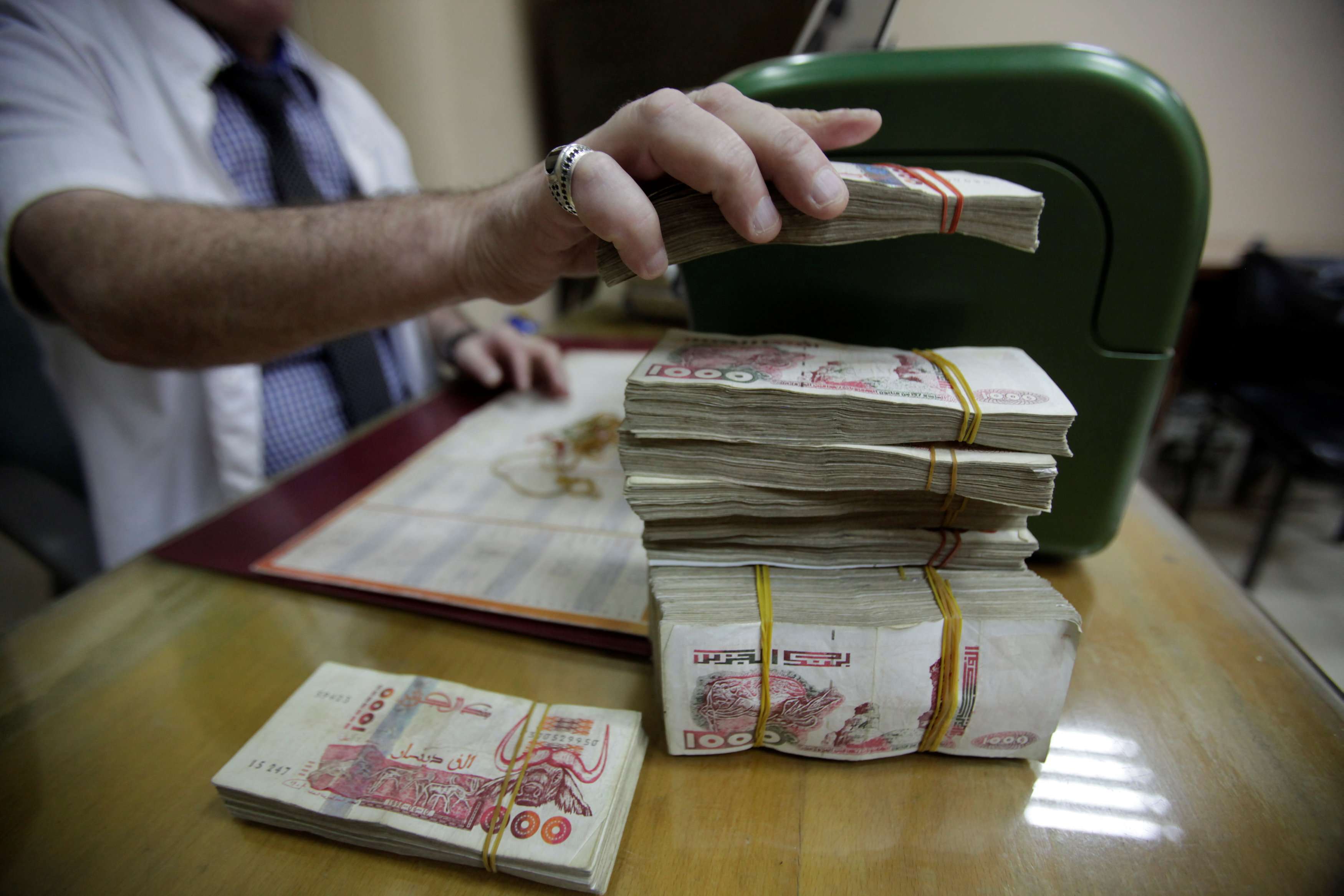 Controversial policies. A man counts Algerian Dinar banknotes in Algiers. (Reuters)