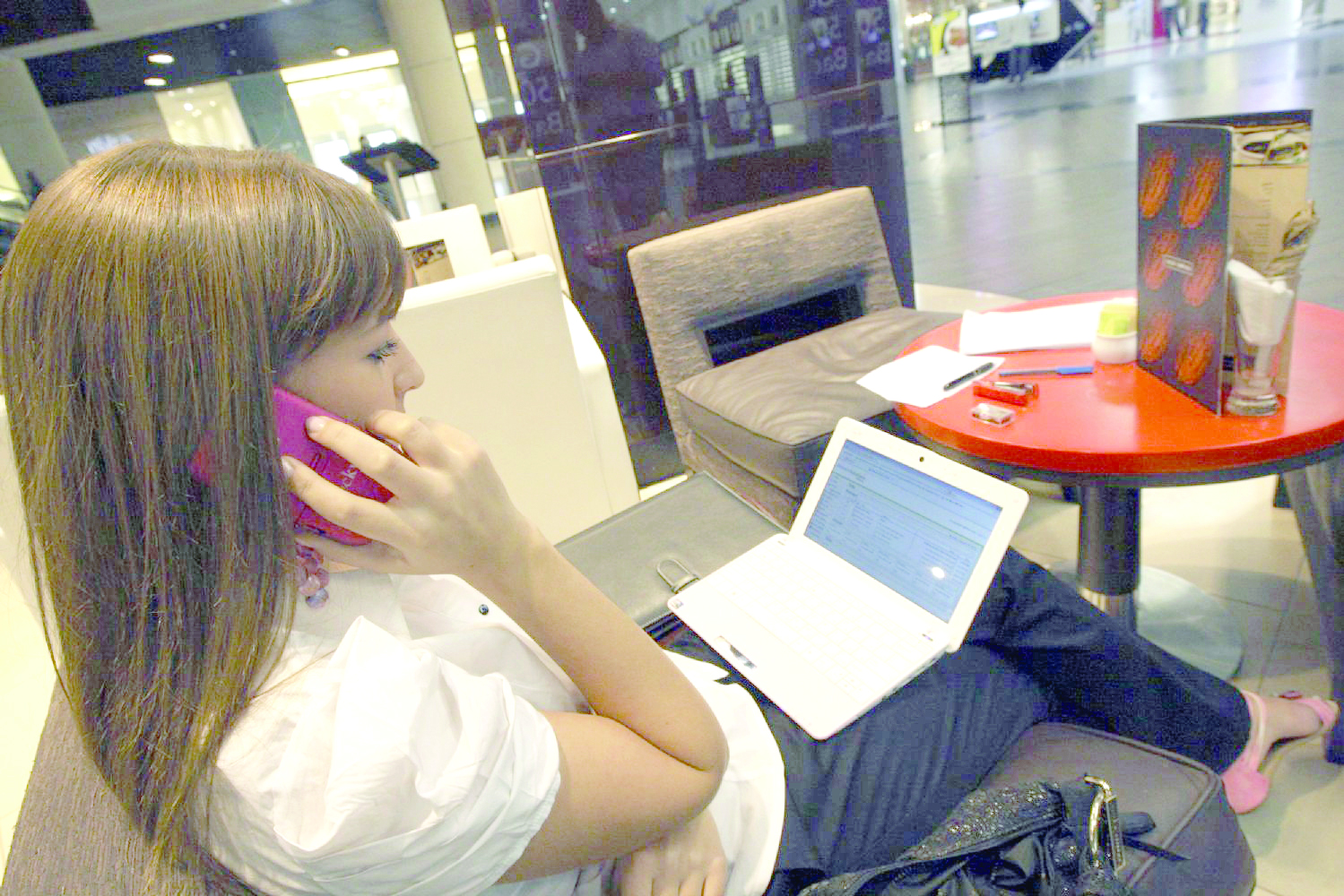 A young Arab woman looks at her laptop while making a phone call at a shopping mall in Dubai. (Reuters)