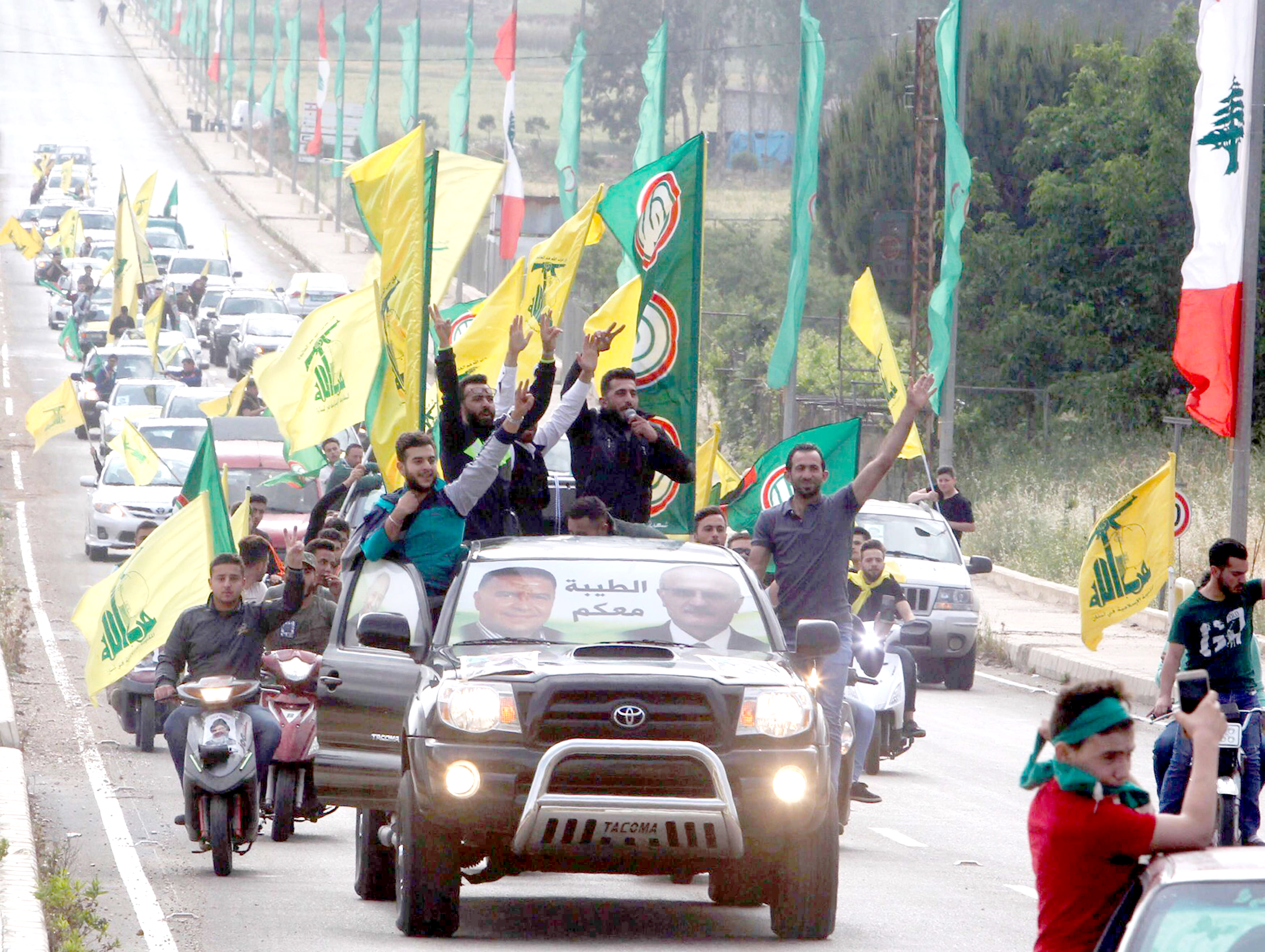 Supporters of Lebanon's Hezbollah and Amal Movement gesture as they ride in a car in Marjayoun, on May 7. (Reuters)