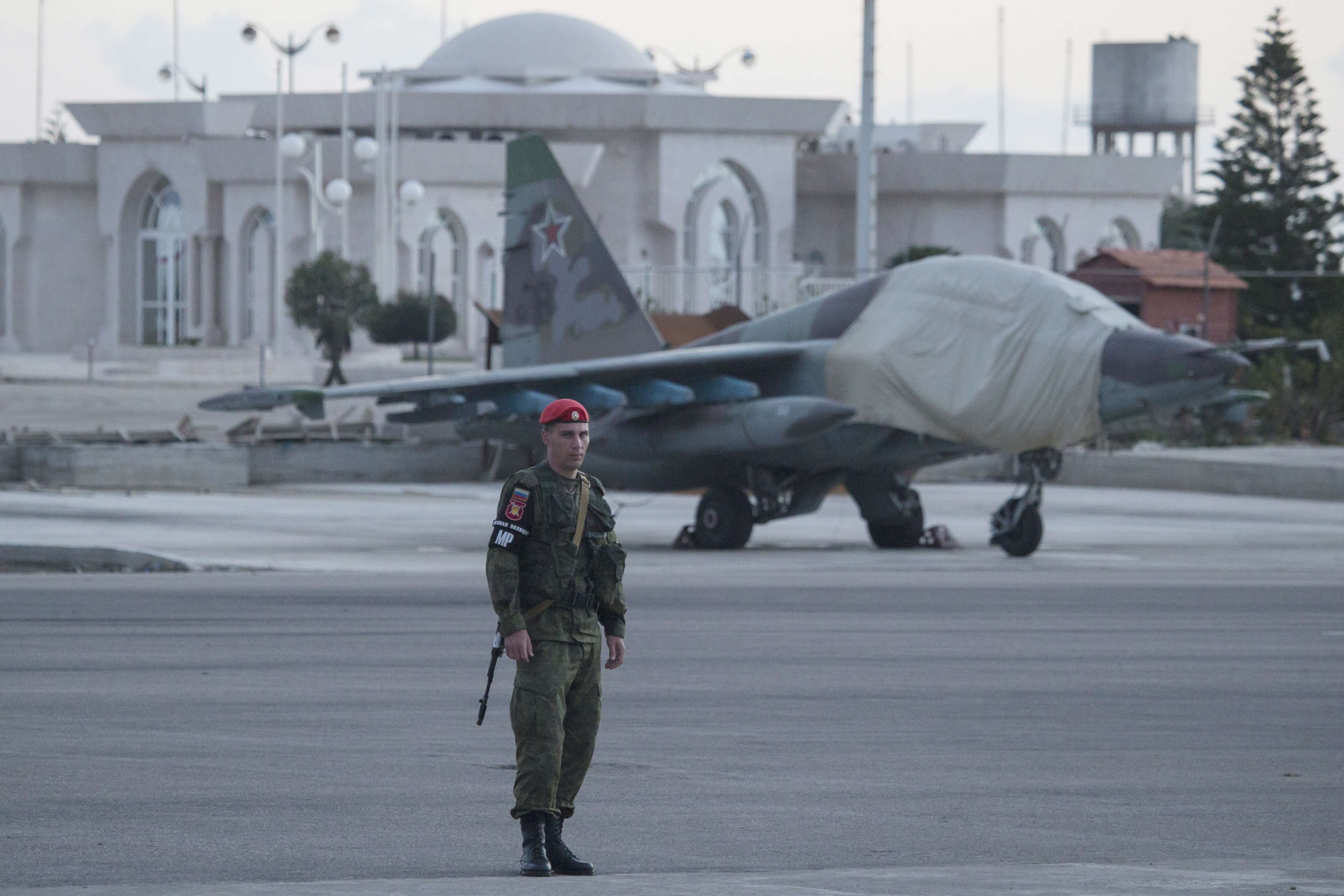 A Russian soldier stands guard as Su-25 ground attack jet is parked at Hmeimim air base in Syria. (AP)