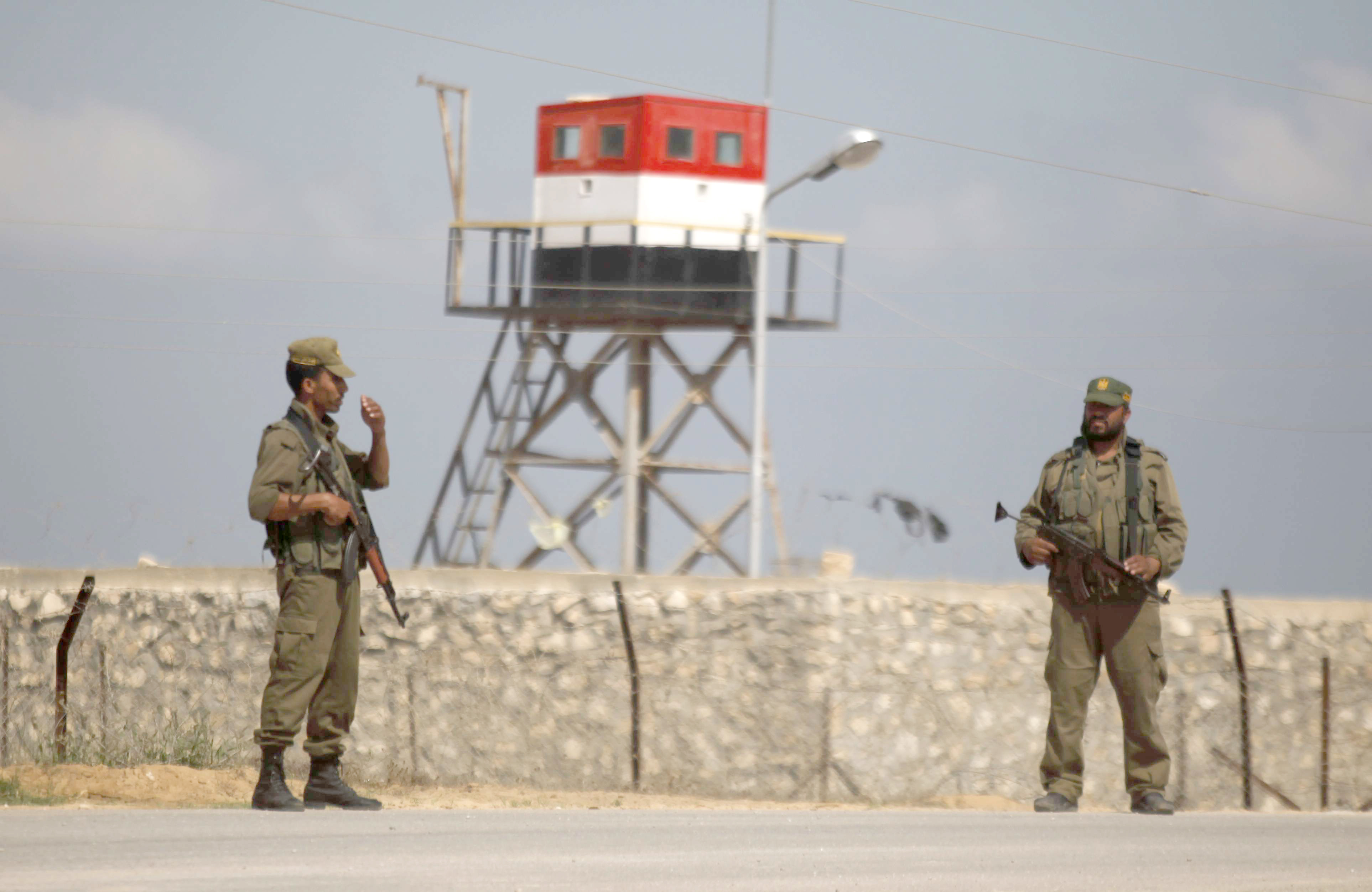 Palestinian Hamas security guards stand near an Egyptian watch tower on the border with Egypt in Rafah. (AP)