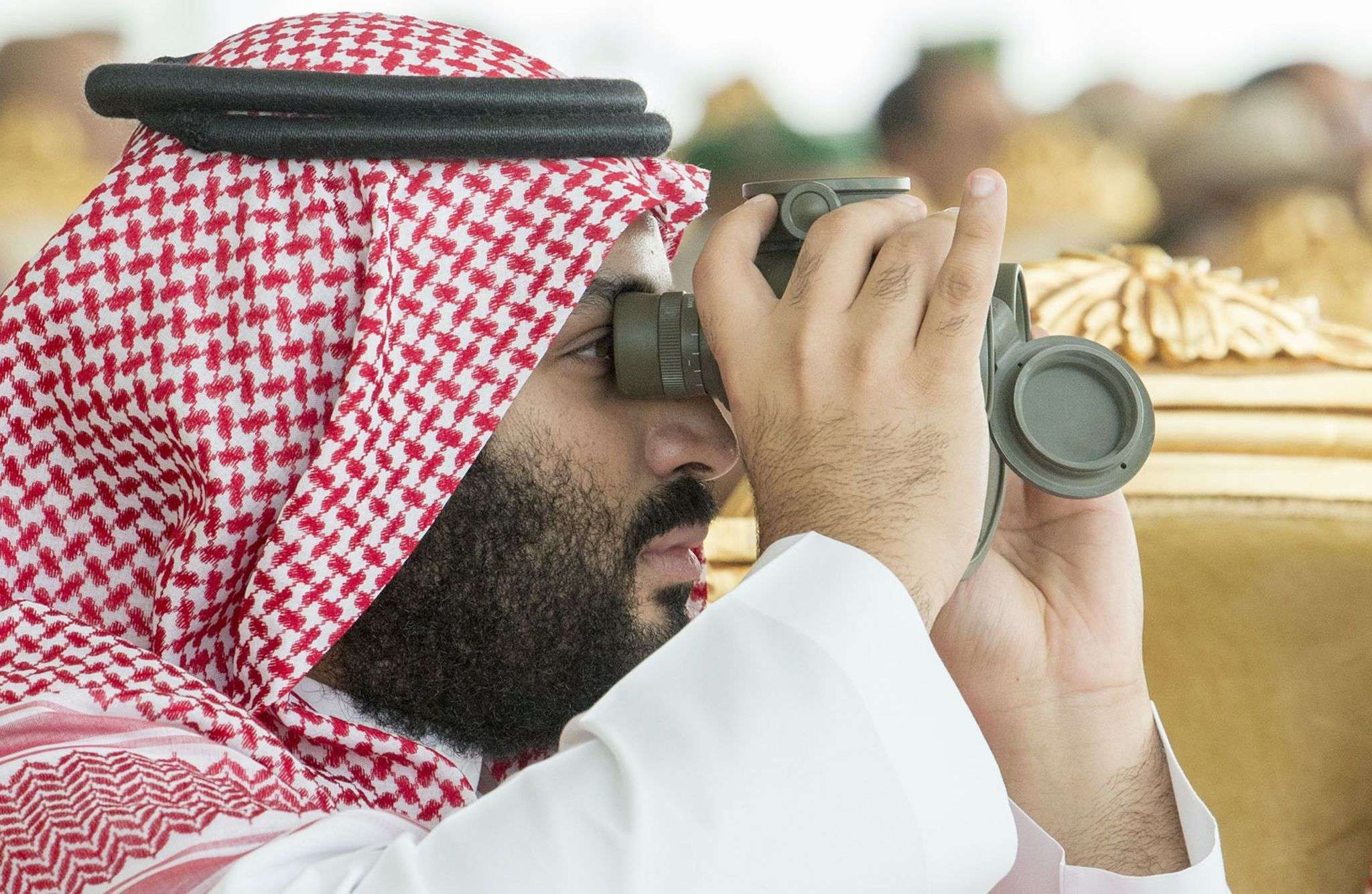 "Saudi Crown Prince Mohammed bin Salman bin Abdulaziz uses binoculars to follow the ""Gulf Shield 1″ military drills, on April 16.  (Saudi Royal Palace)"
