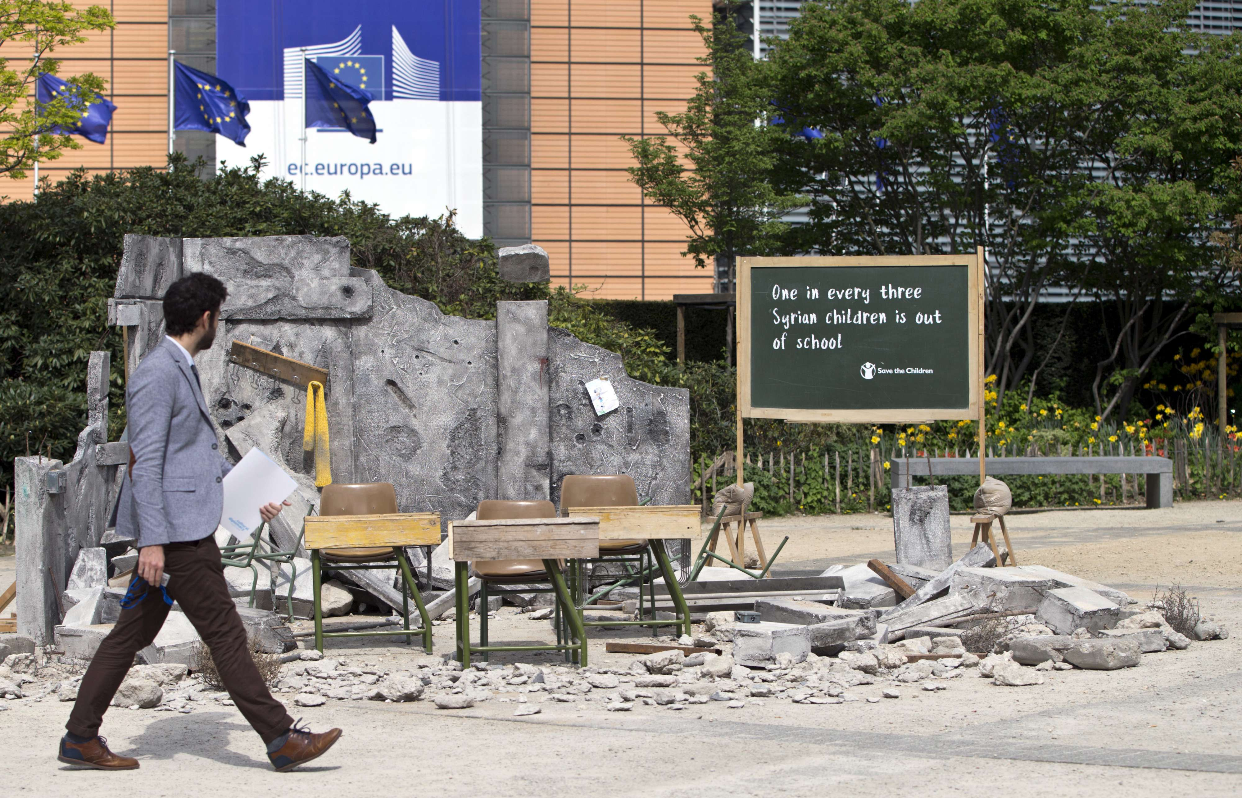 A man walks by a set designed to look like a bombed out Syrian classroom in front of EU headquarters in Brussels, on April 23.  (AP)